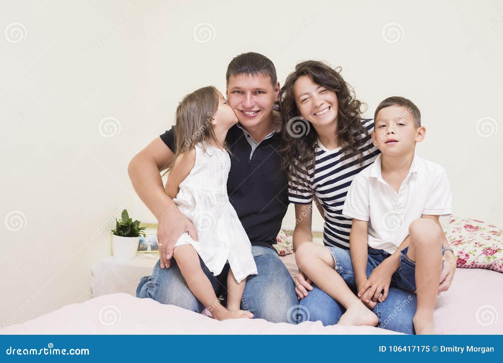 Stående av den lyckliga Caucasian familjen med två ungar som tillsammans poserar
