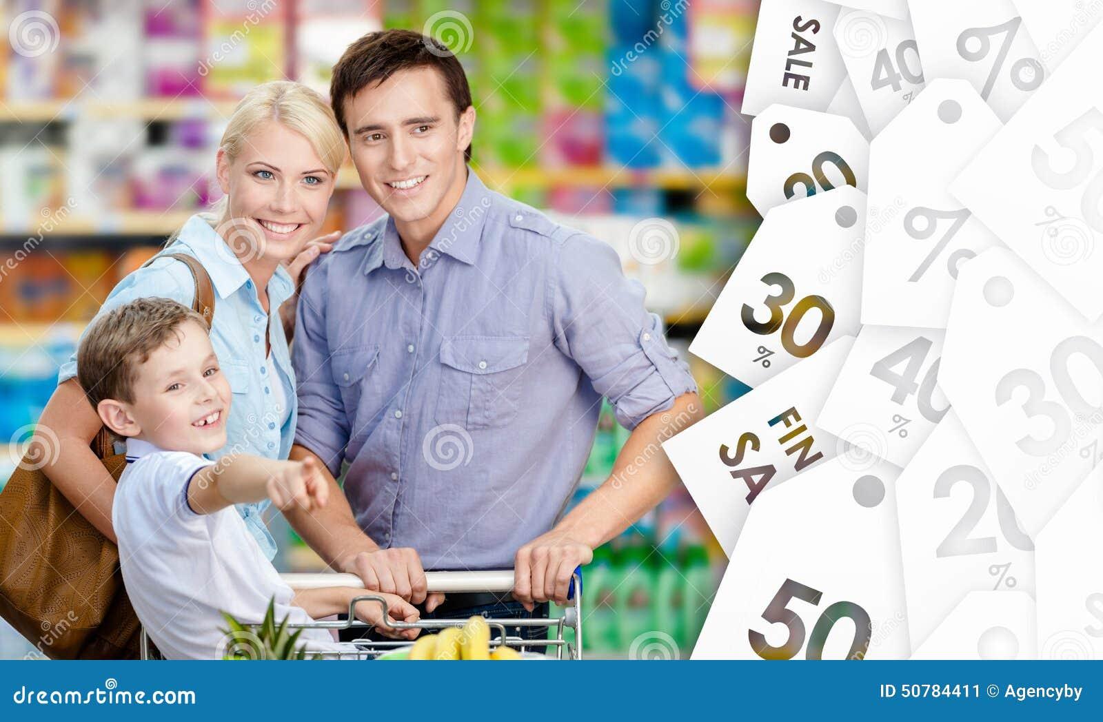 Stående av den lyckliga familjen i shoppa
