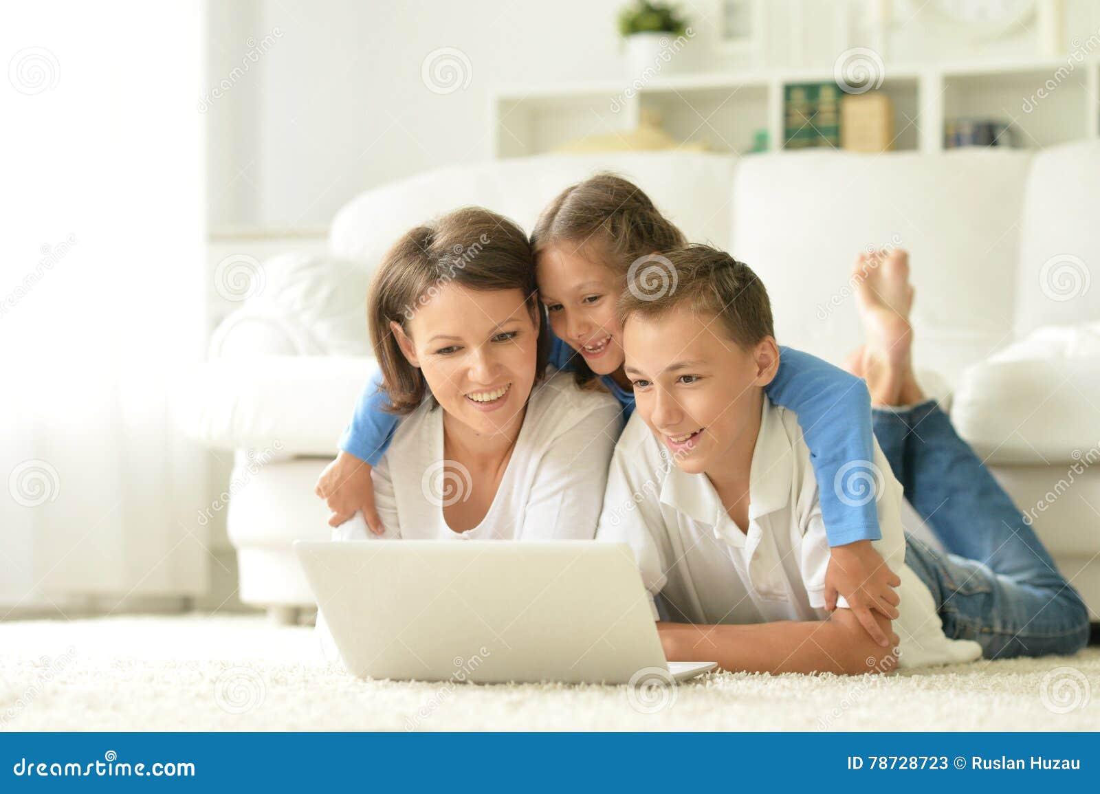 Stående av den lyckliga familjen med bärbara datorn