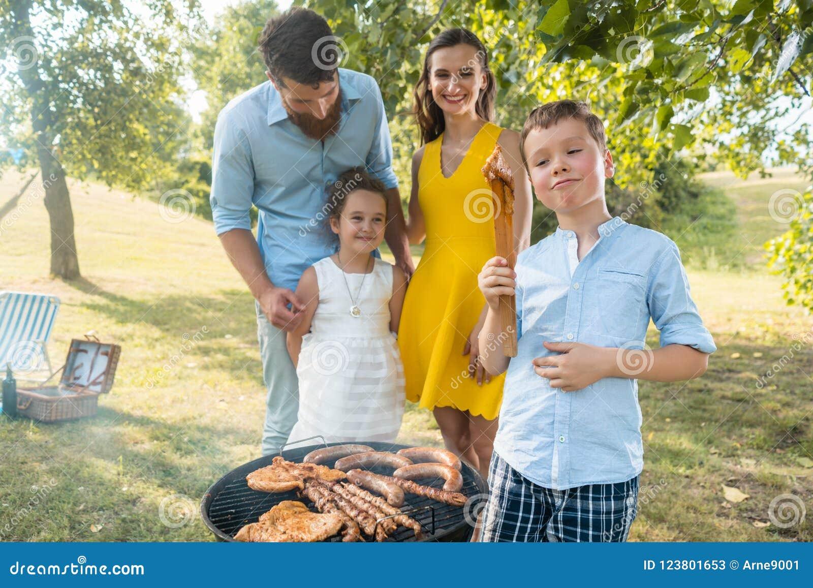 Stående av den lyckliga familjen med två barn som utomhus står nära en grillfest