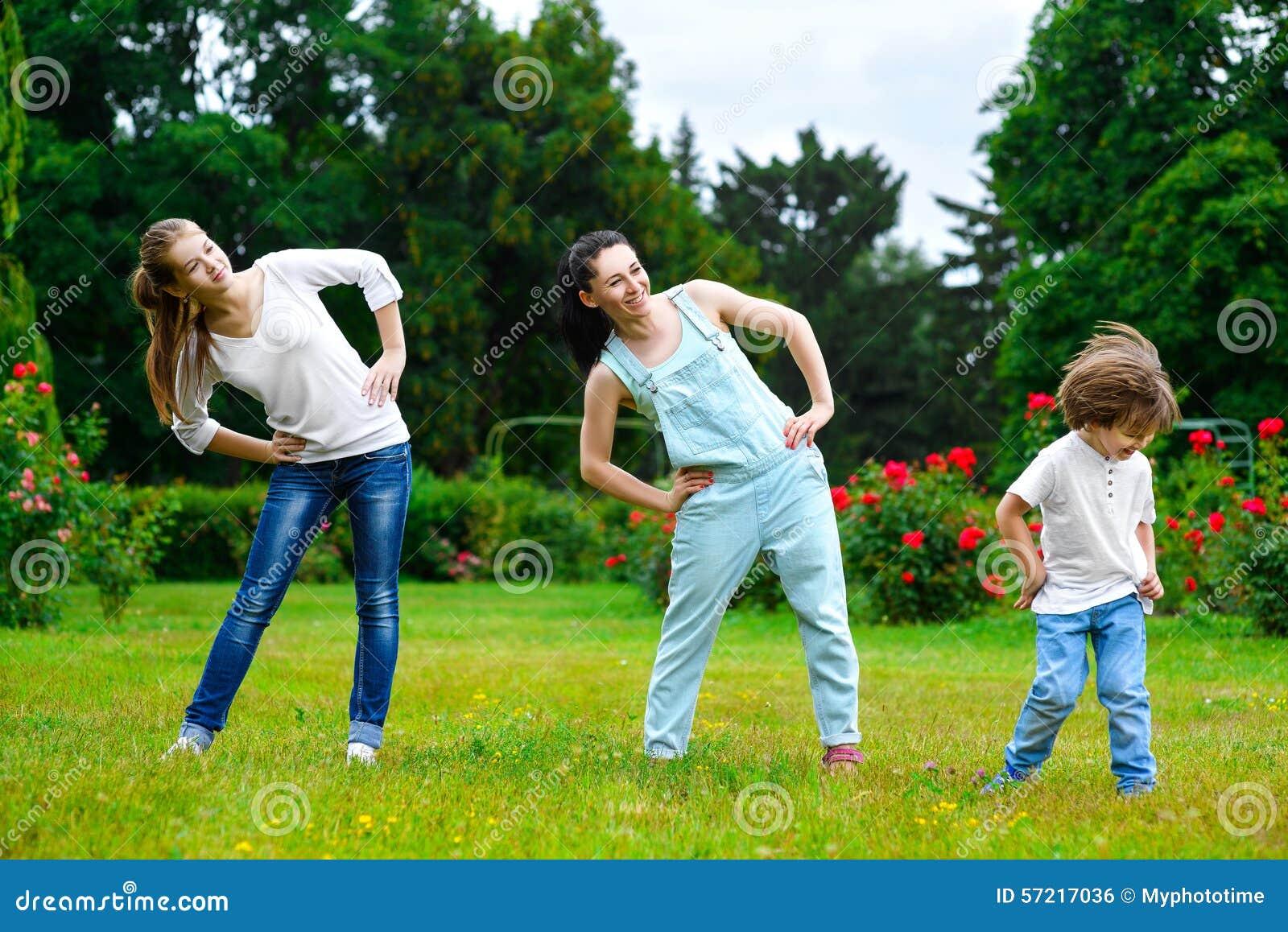 Stående av den lyckliga familjen som gör fysisk övning