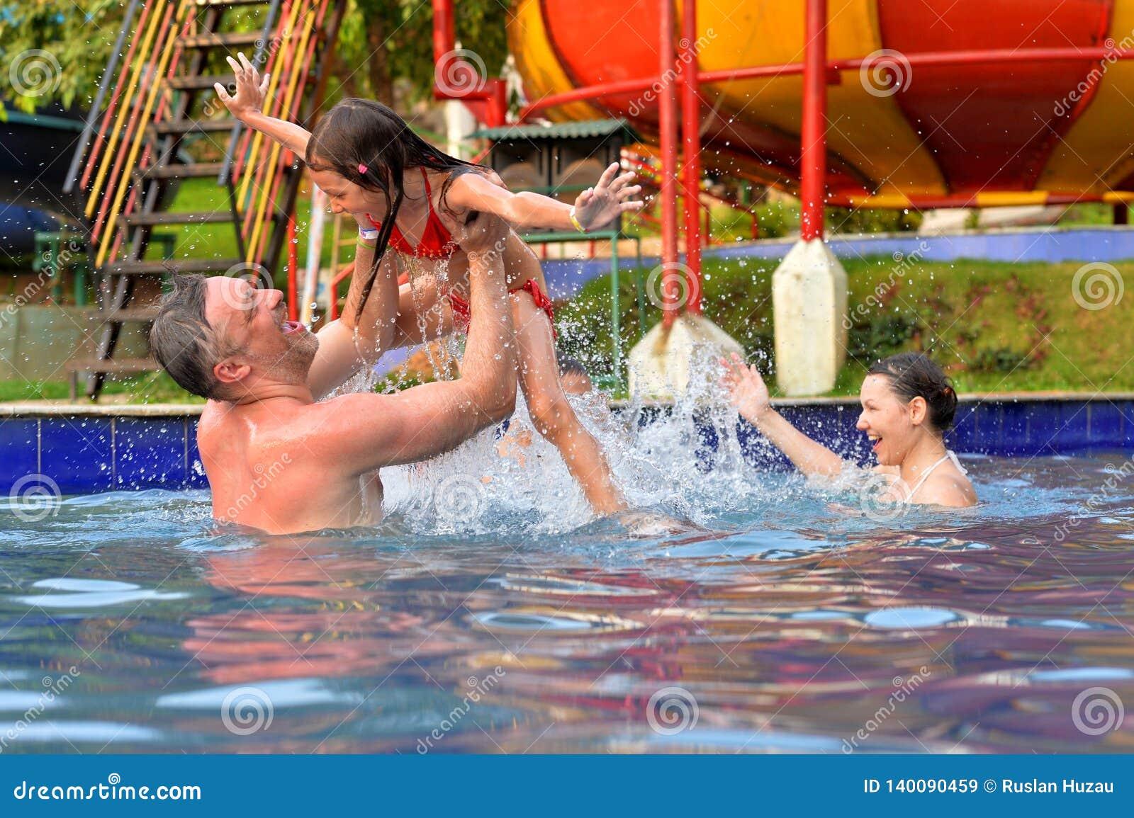 Stående av den lyckliga familjen som har gyckel i simbassäng i sommar