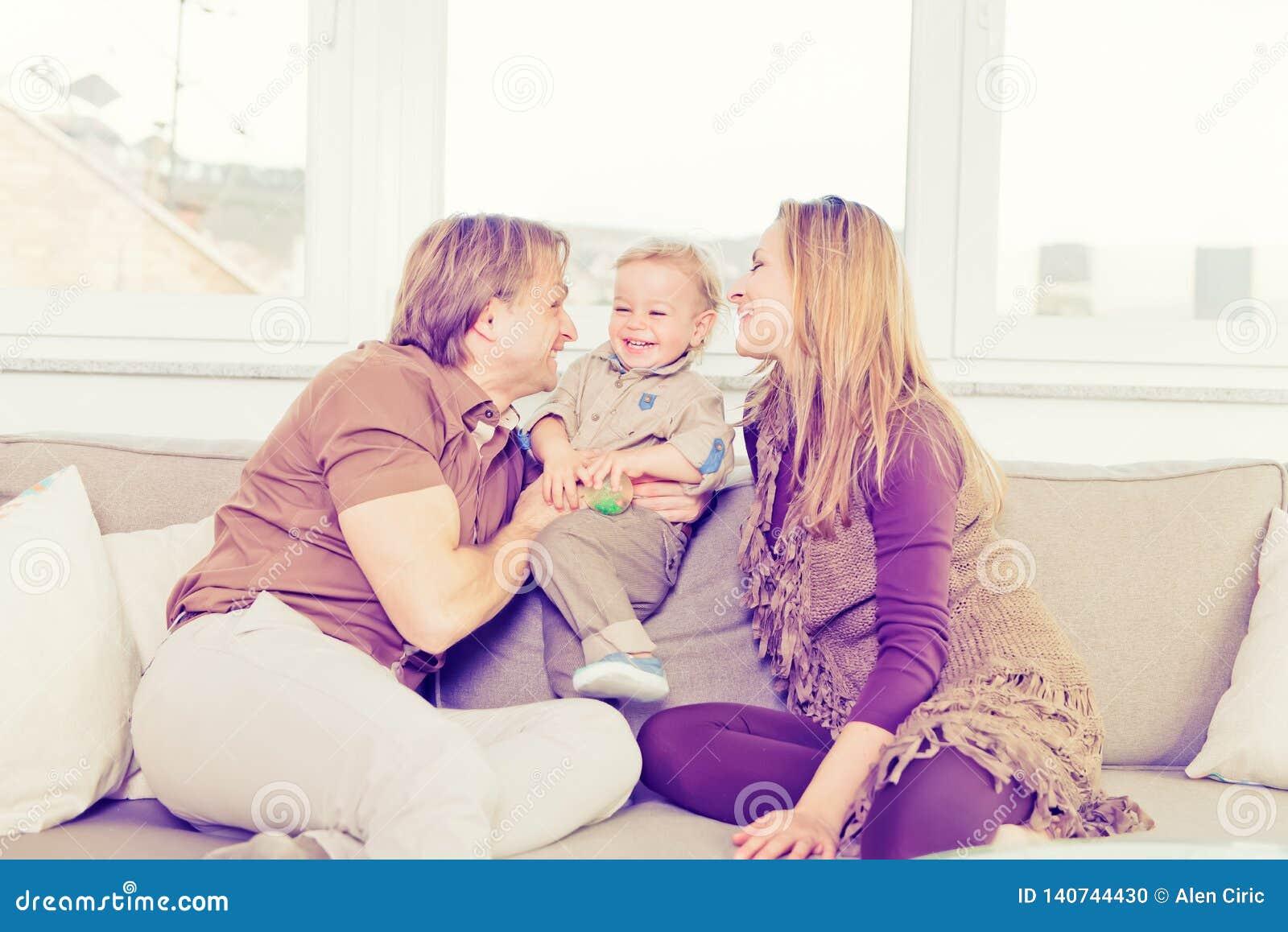 Stående av den lyckliga familjen som sitter på soffan och spela