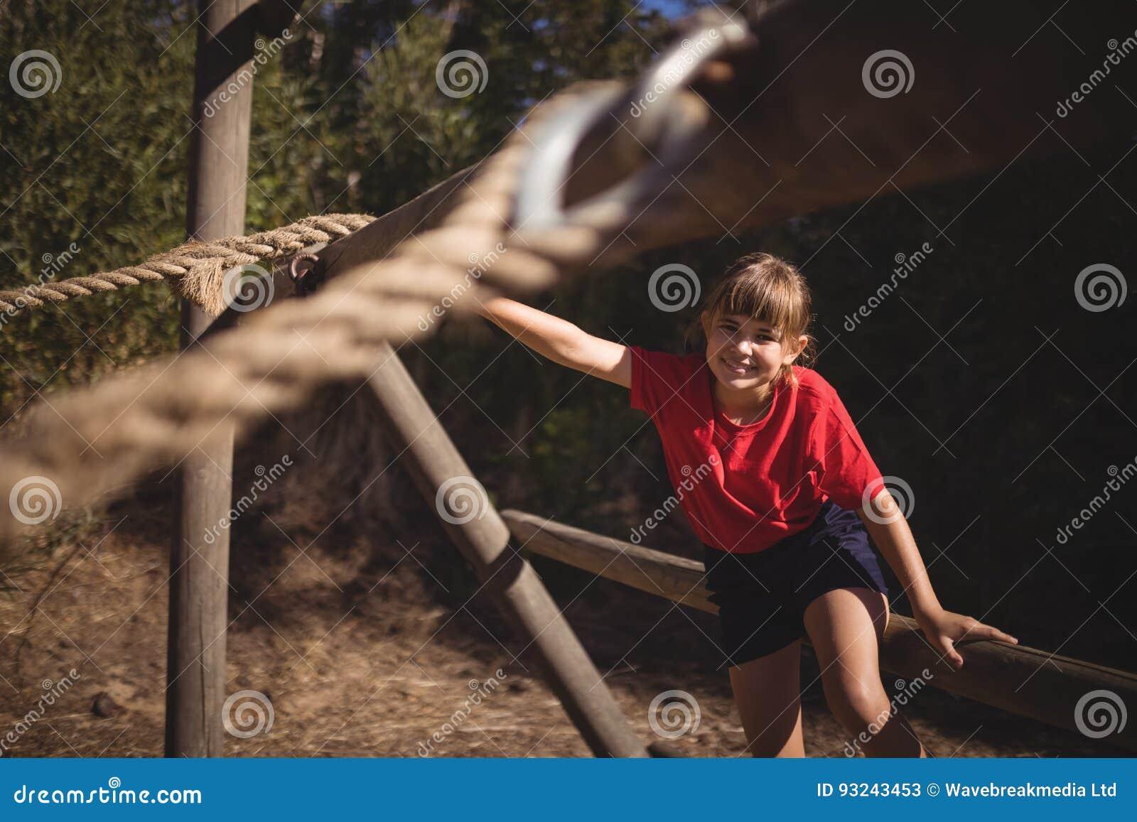 Stående av den lyckliga flickan som övar på utomhus- utrustning under hinderkurs