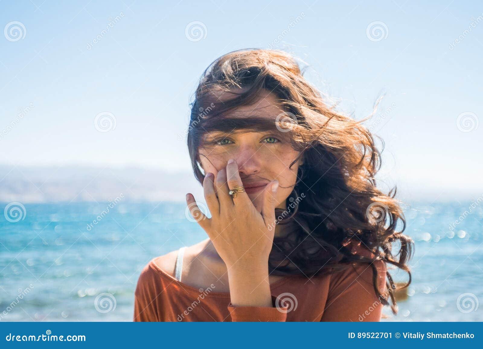 Stående av den lyckliga le unga kvinnan på strand- och havsbakgrund Vindlekar med långt hår för flicka