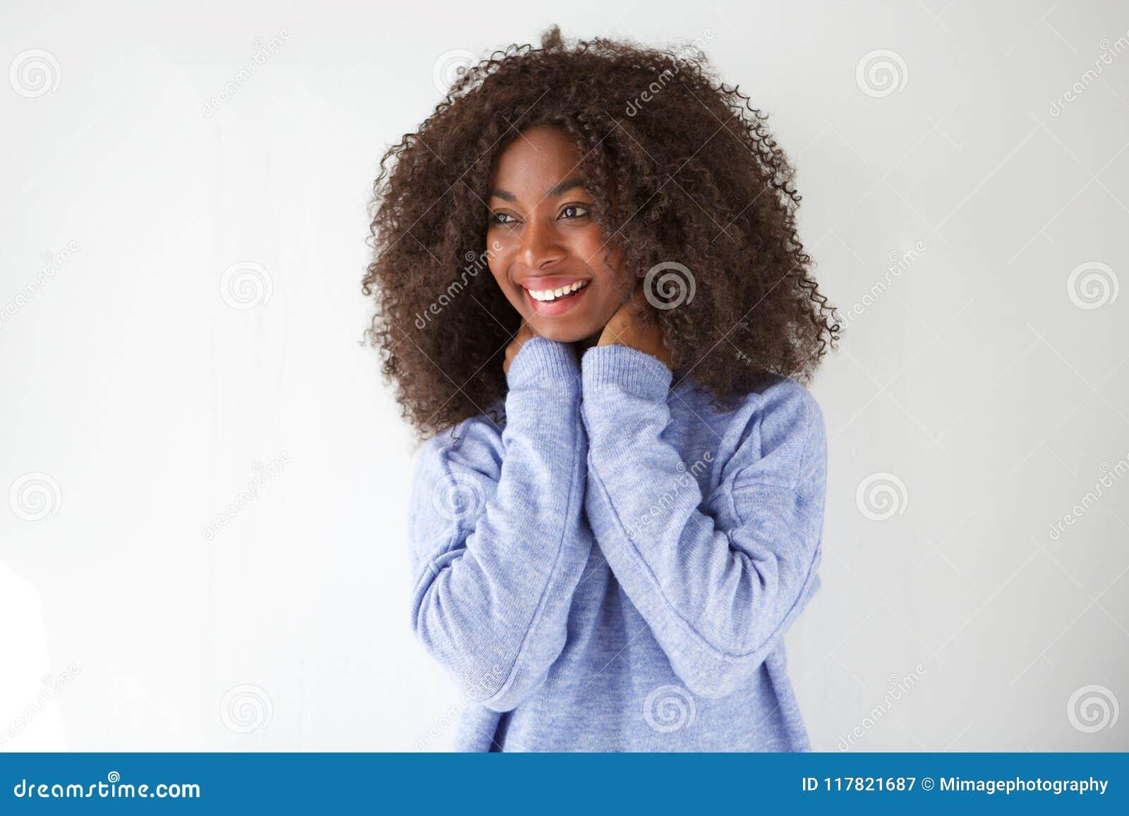 Stående av den lyckliga unga afrikanska kvinnan som skrattar och ser bort mot vit bakgrund