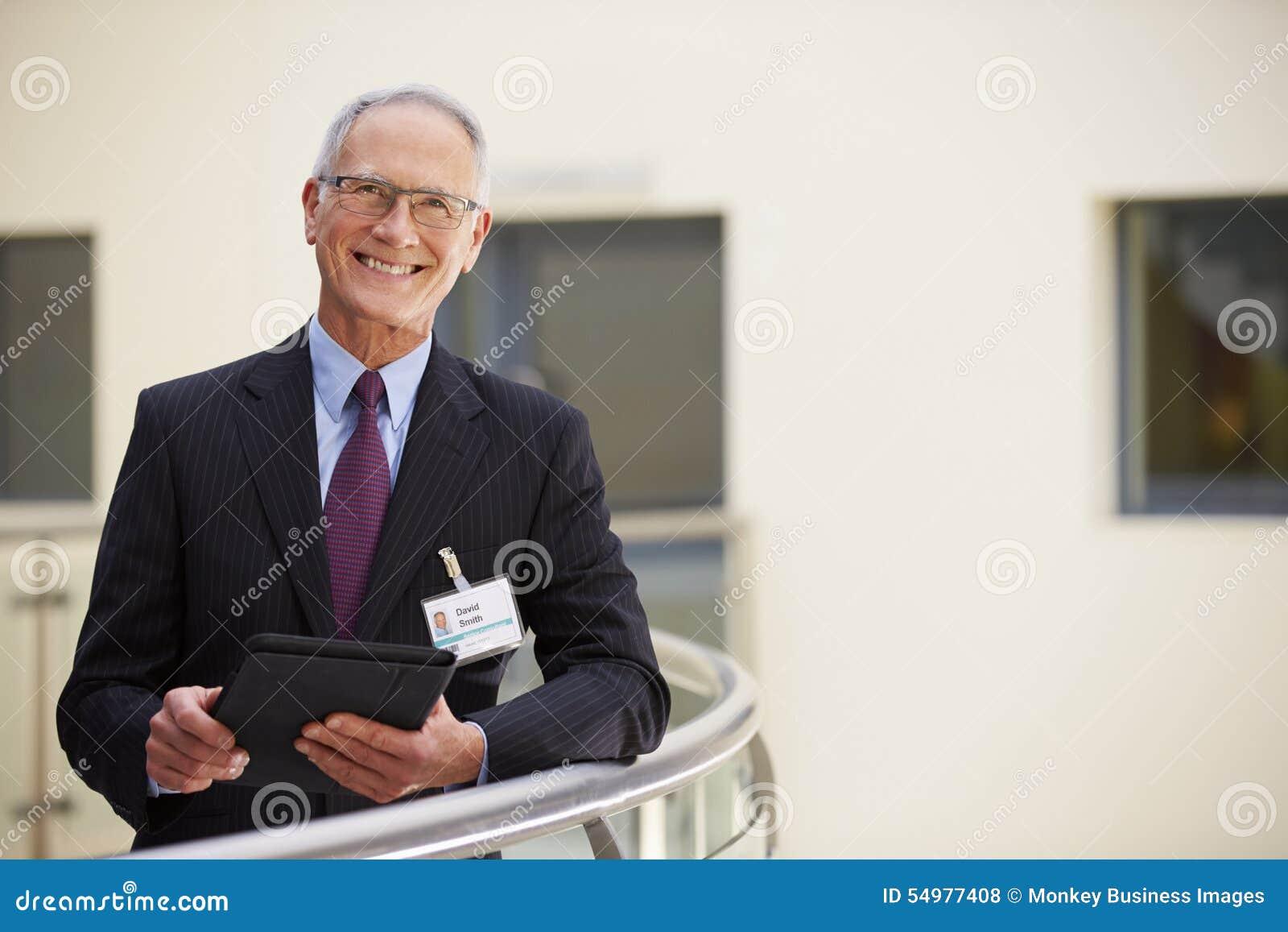 Stående av den manliga konsulenten Using Digital Tablet i sjukhus