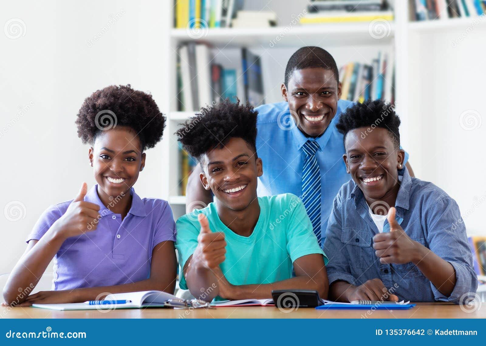 Stående av den manliga läraren med afrikansk amerikanstudenter