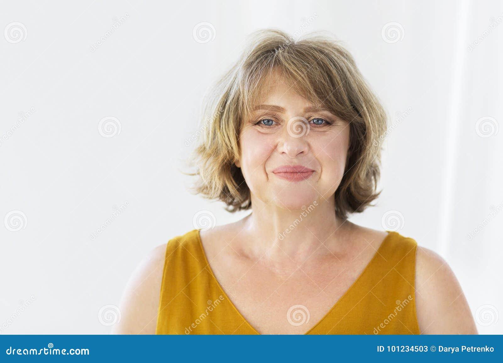 Stående av den mellersta ålderkvinnan i rummet