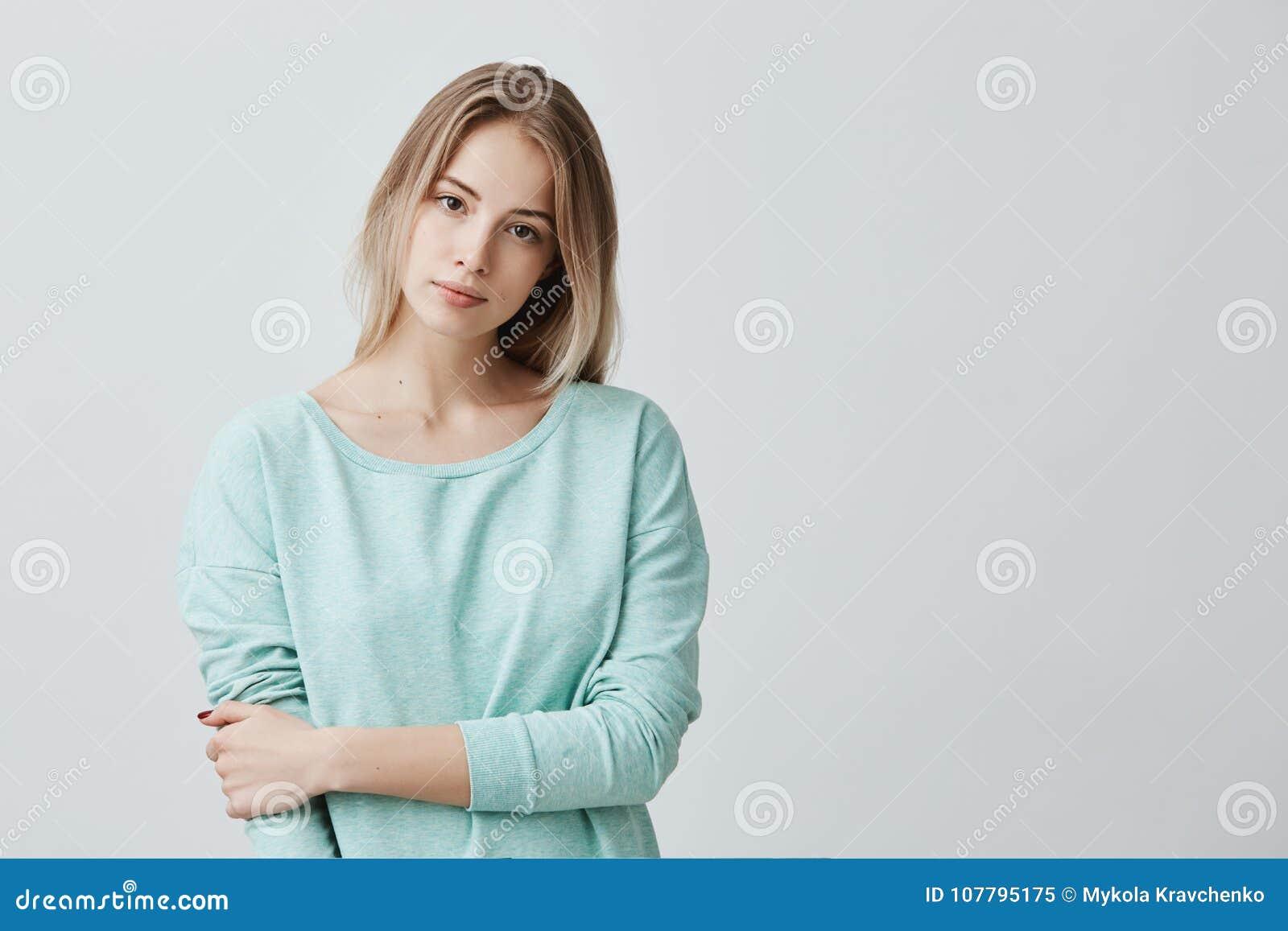 Stående av den mjuka blonda europeiska kvinnan för barn med bärande ljus för sund hud - blått lång-mufde att se kameran med