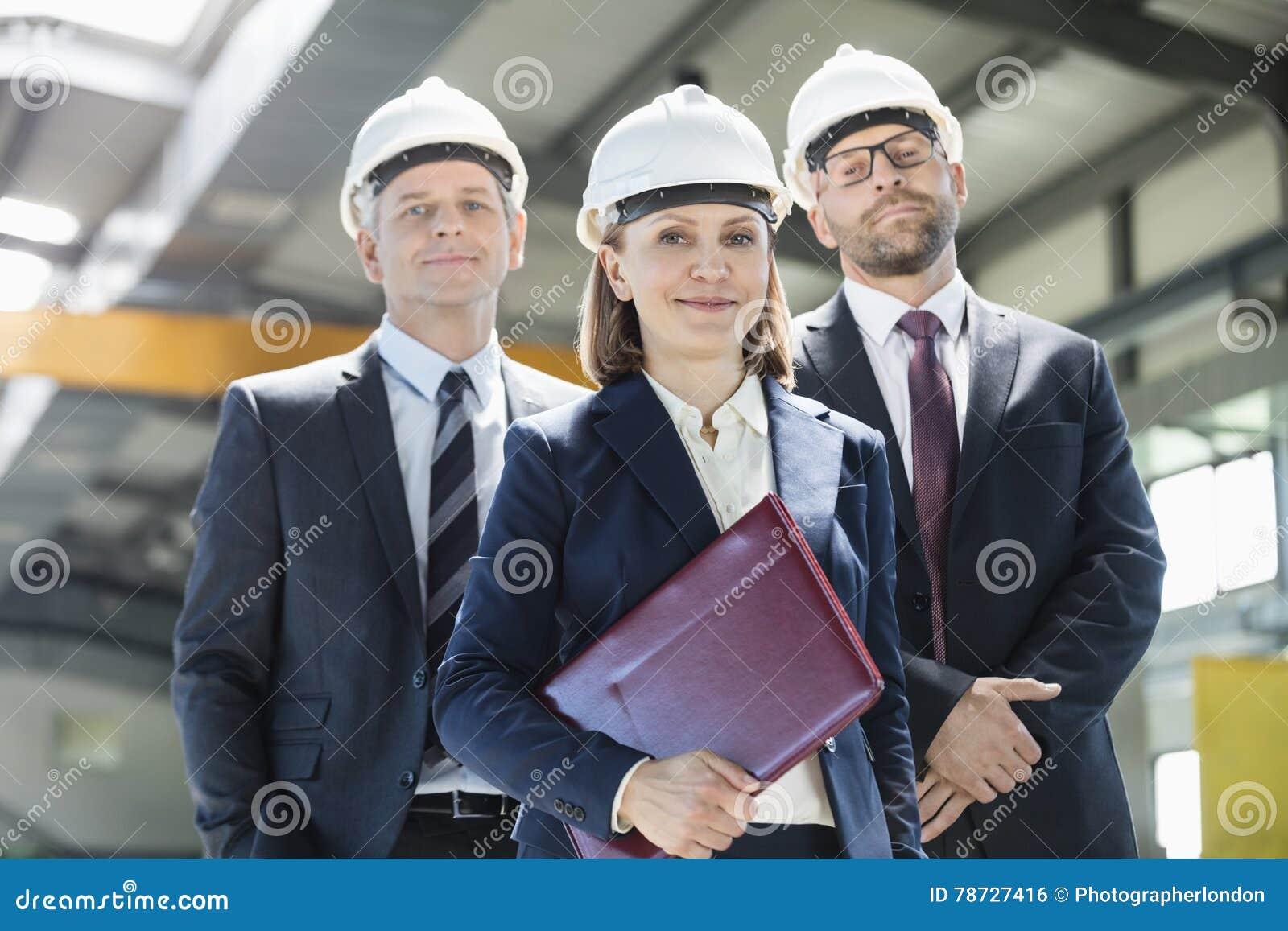 Stående av den mogna affärskvinnan med manliga kollegor i metallbransch
