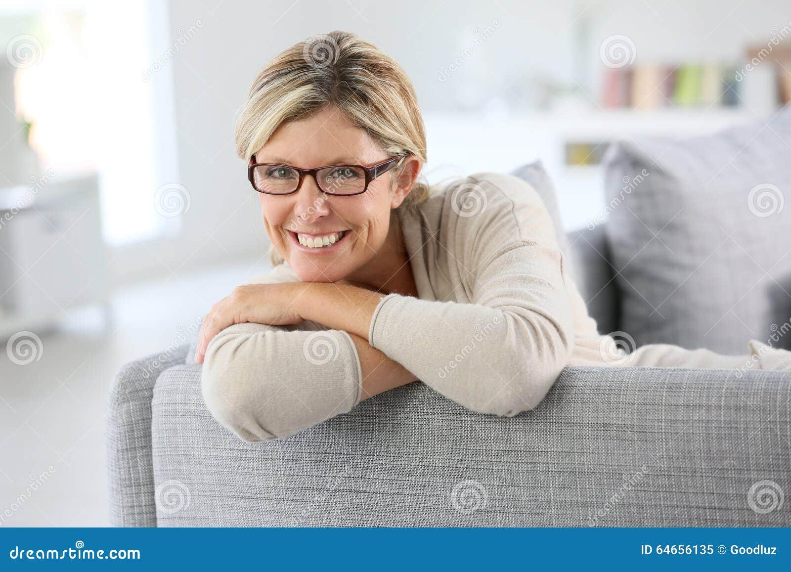 Stående av den mogna kvinnan på att koppla av för soffa