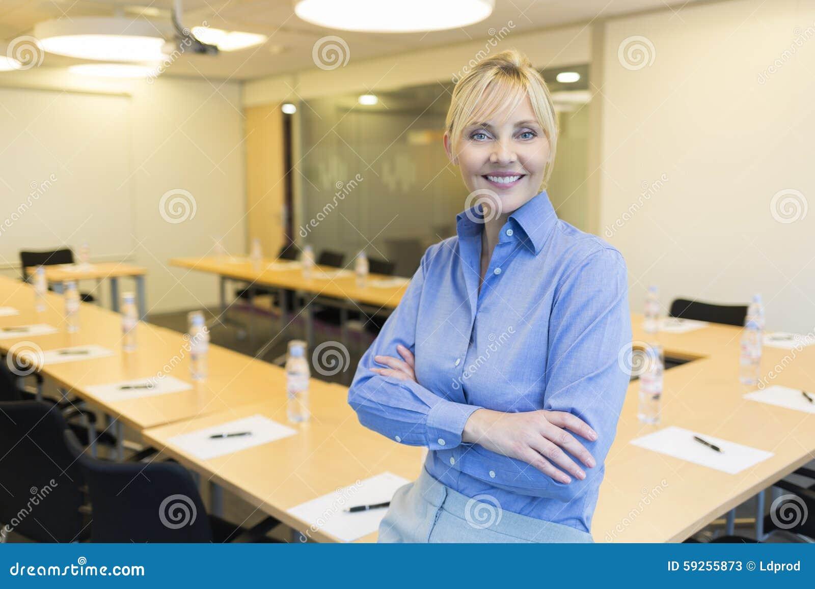 Stående av den nätta affärskvinnan i mötesrum