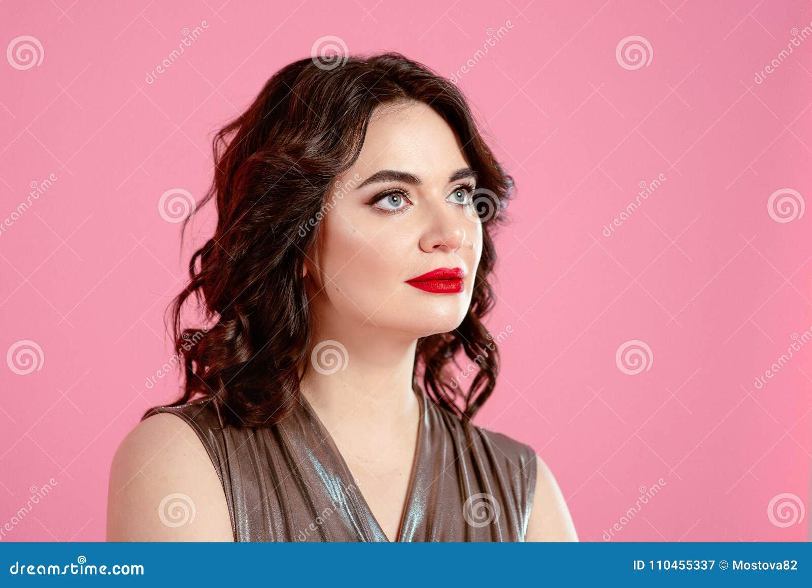 Stående av den nätta attraktiva unga kvinnan för brunett i silverdiskooveraller