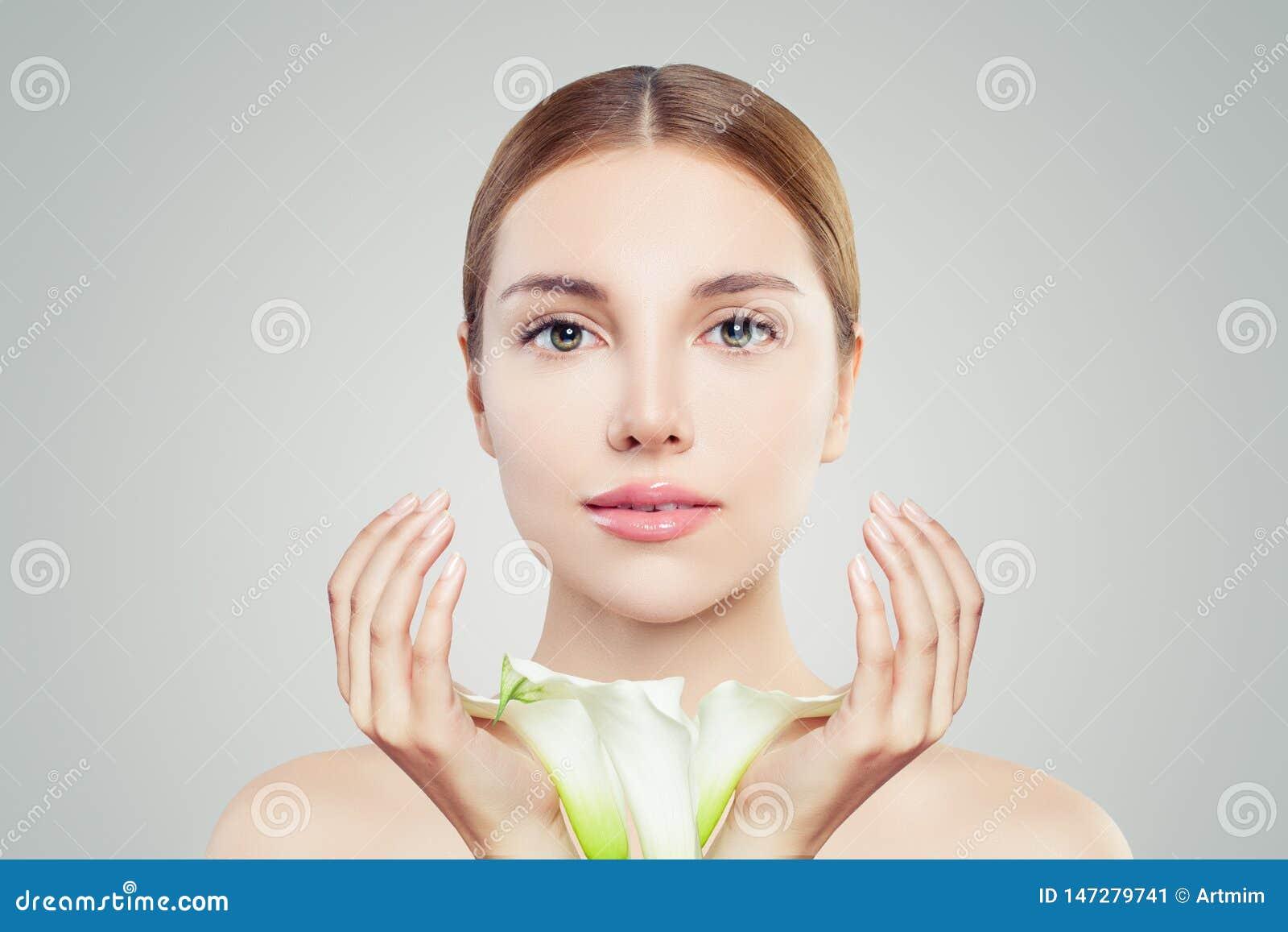 Stående av den nätta kvinnan med klar hud och blommor Skincare och ansikts- behandlingbegrepp