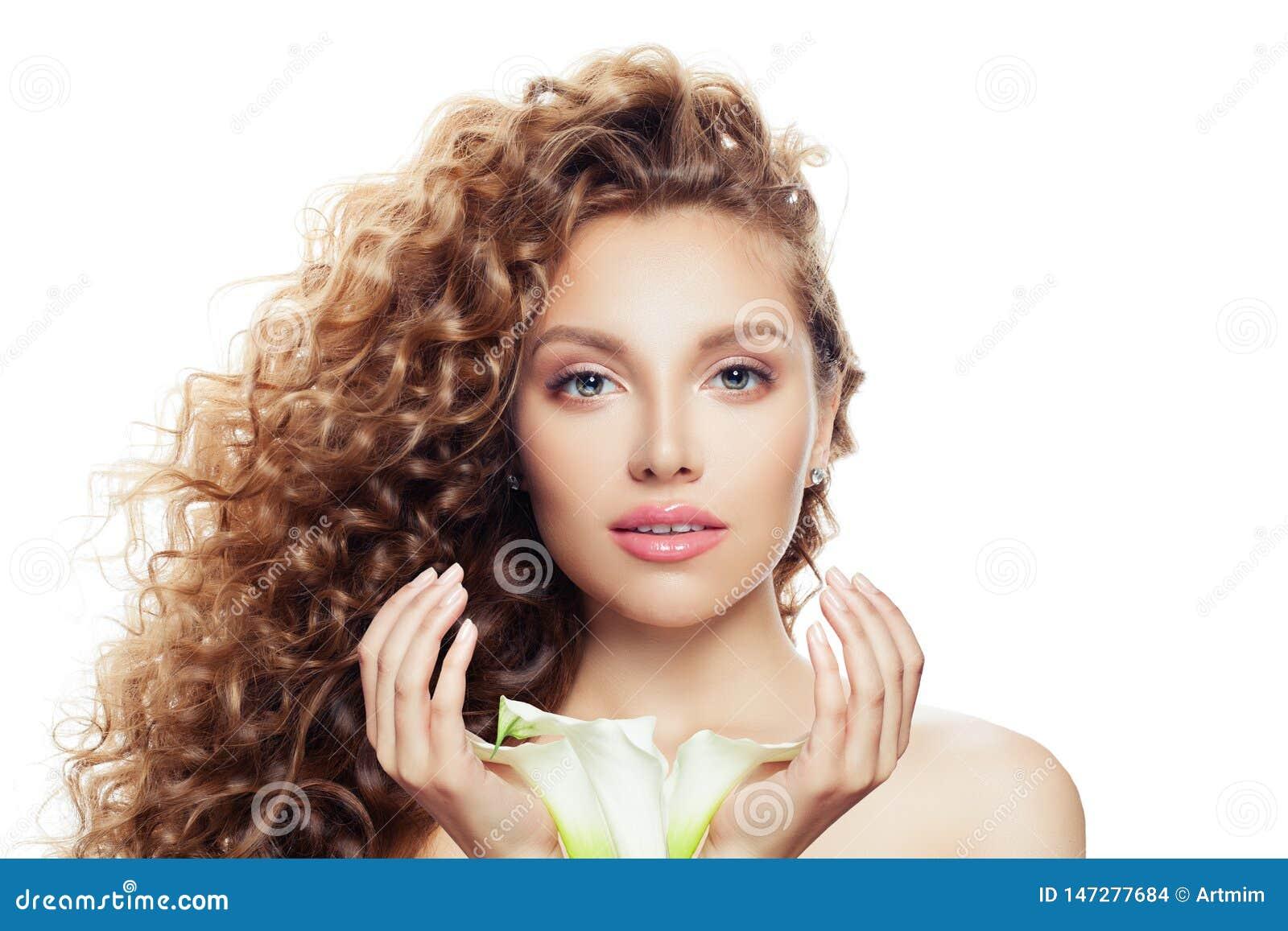 Stående av den nätta kvinnan med långt lockigt hår, klar hud och liljablomman i hennes händer som isoleras på vit bakgrund