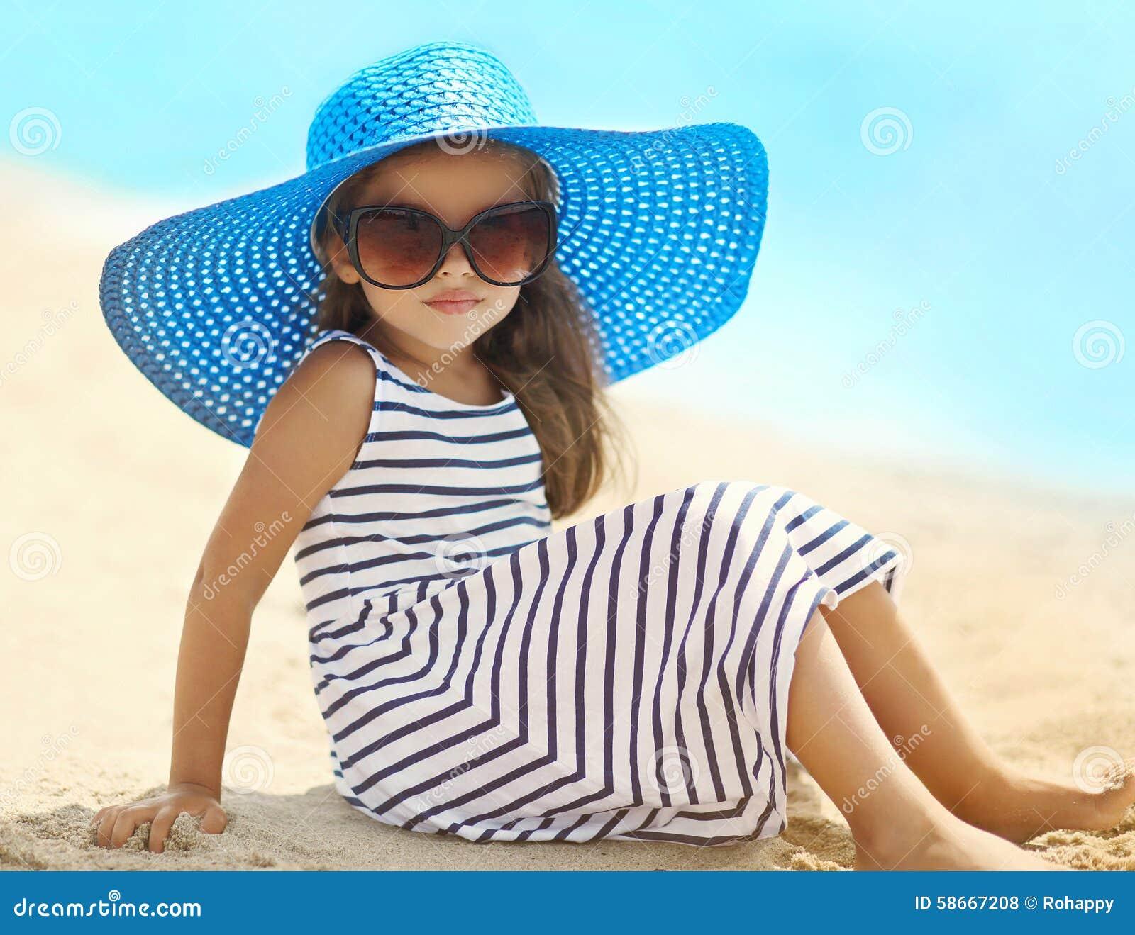 Stående av den nätta lilla flickan i en randig klänning- och sugrörhatt som kopplar av att vila på stranden nära havet