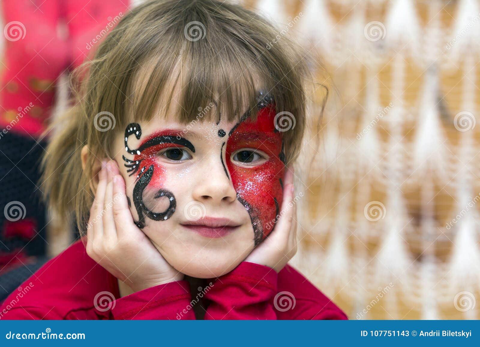 Stående av den nätta lilla flickan med fjärilsmålning på hennes fa