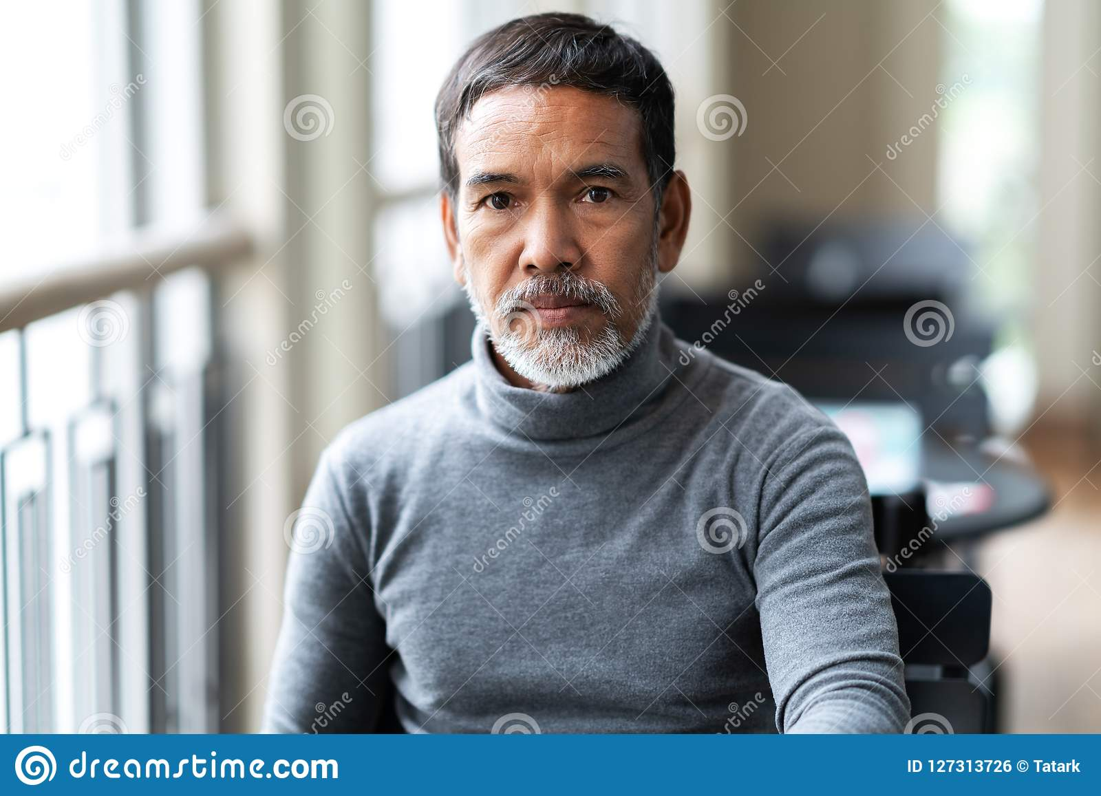 Stående av den olyckliga ilskna mogna asiatiska mannen med det stilfulla korta skägget som ser cemera med negativt misstänksamt
