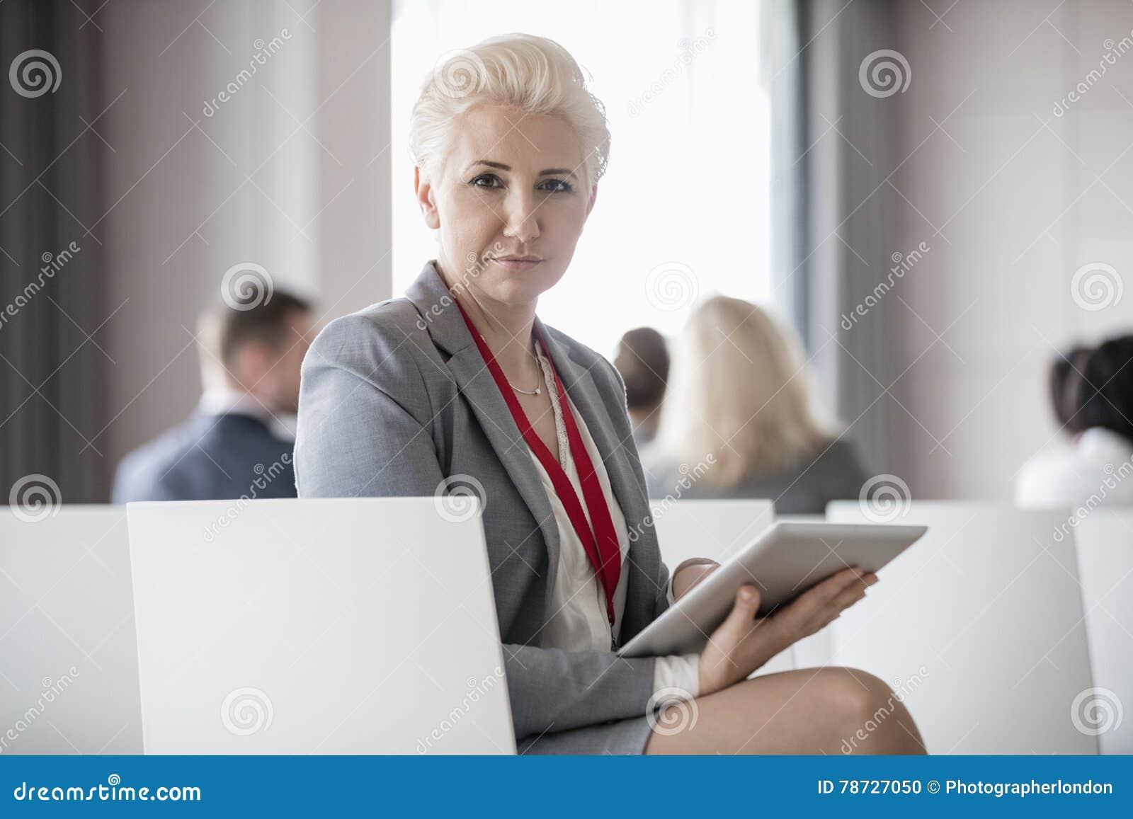 Stående av den säkra affärskvinnan som rymmer den digitala minnestavlan, medan sitta i seminariumkorridor