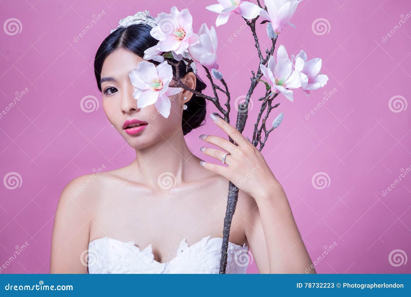 Stående av den säkra bruden som rymmer konstgjorda blommor mot rosa bakgrund