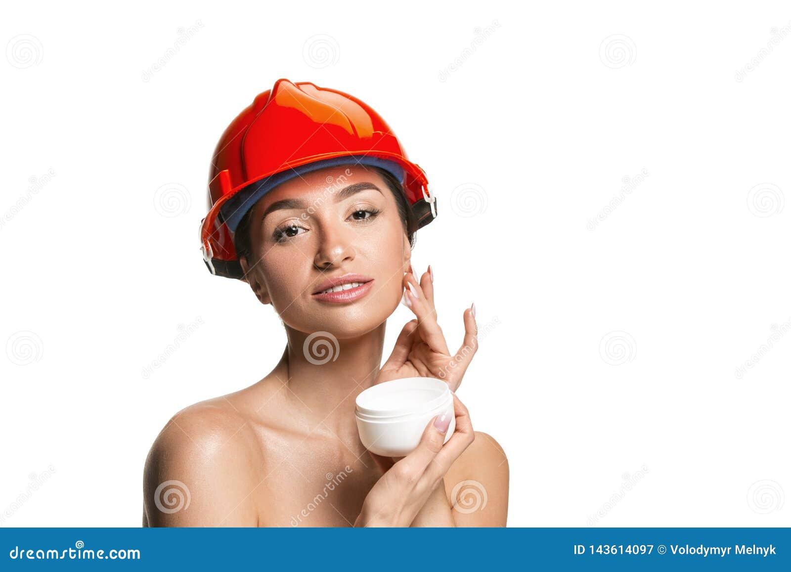Stående av den säkra kvinnliga arbetaren i orange hjälm
