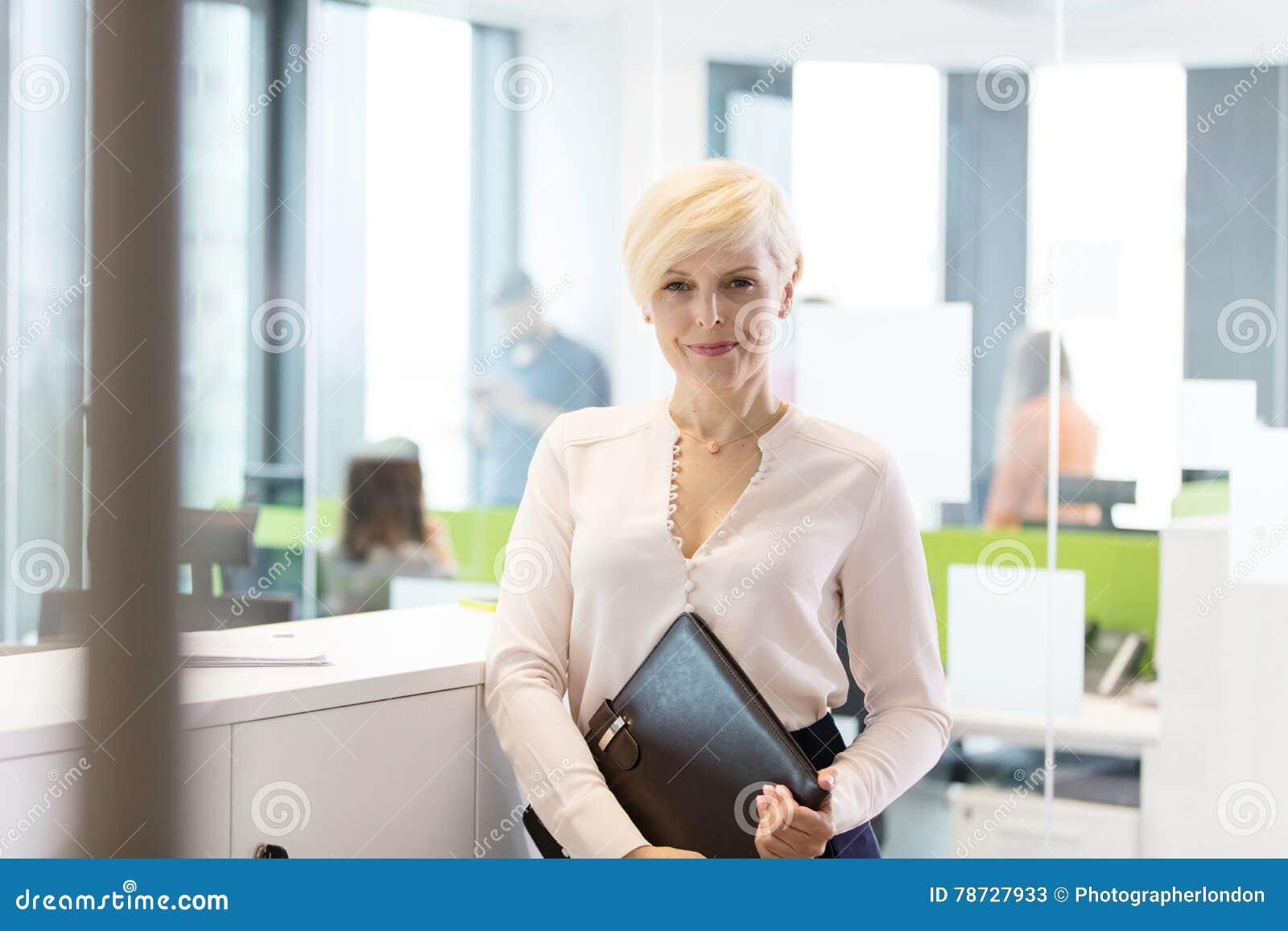 Stående av den säkra mogna affärskvinnan med mappen i regeringsställning