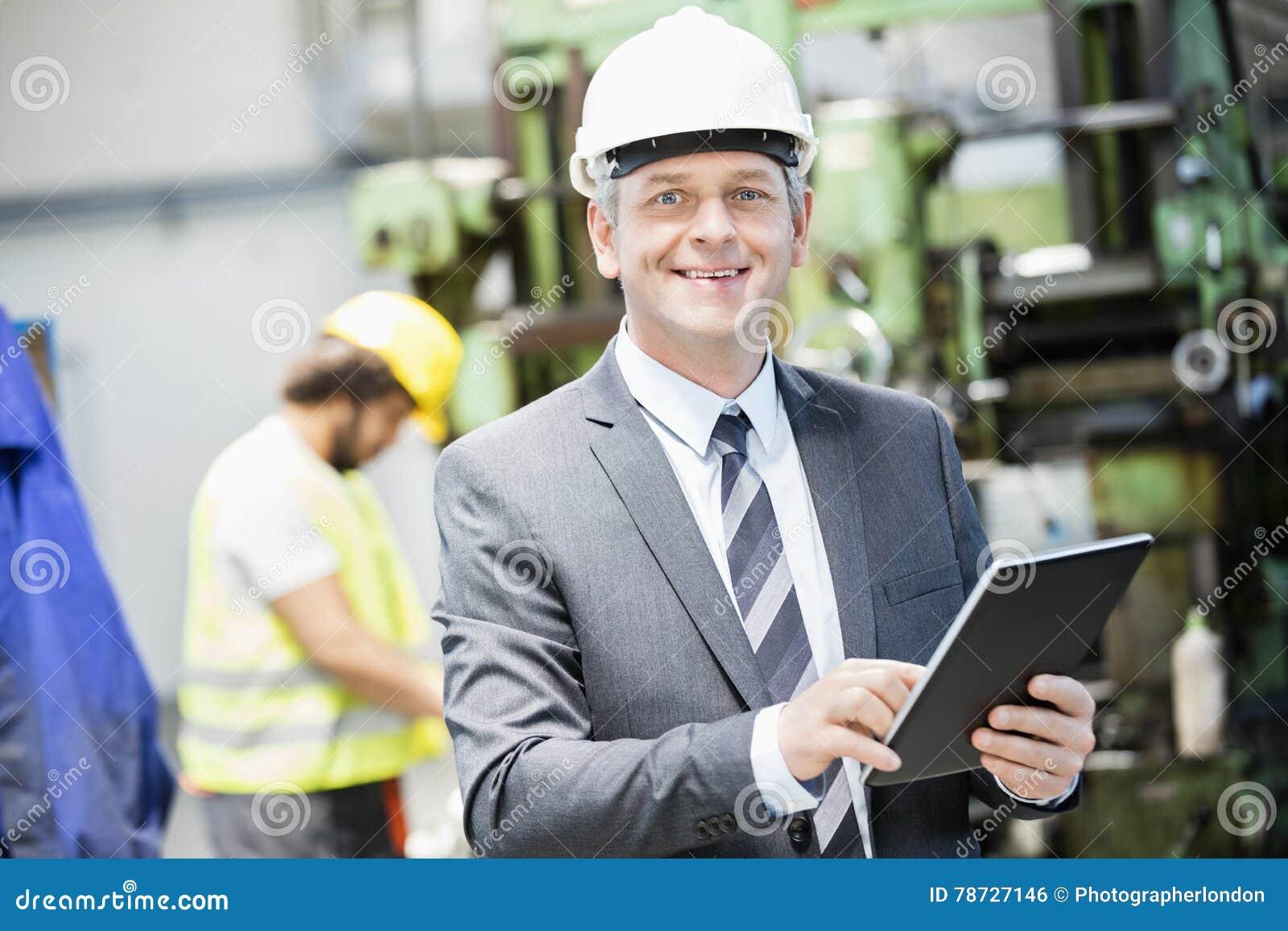 Stående av den säkra mogna affärsmannen som använder den digitala minnestavlan med arbetaren i bakgrund på fabriken