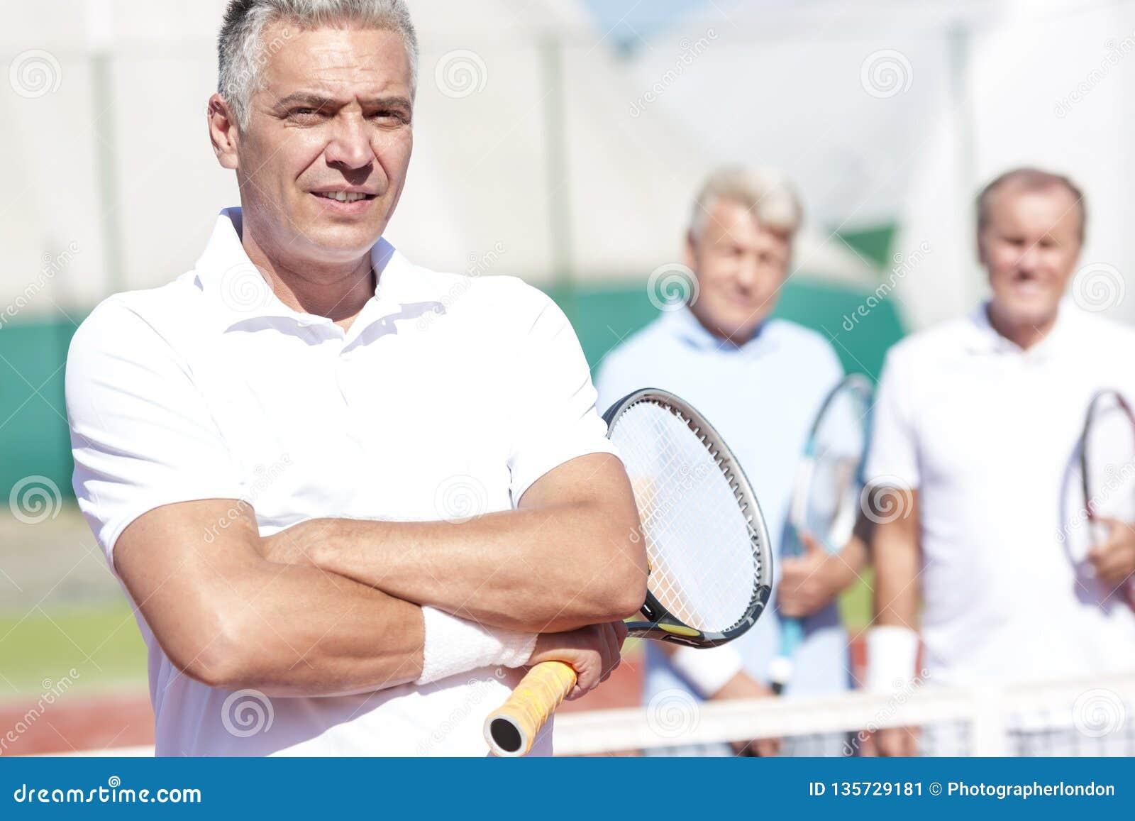 Stående av den säkra mogna mannen som rymmer tennisracket, medan stå med armar som korsas mot vänner på domstolen under solig dag
