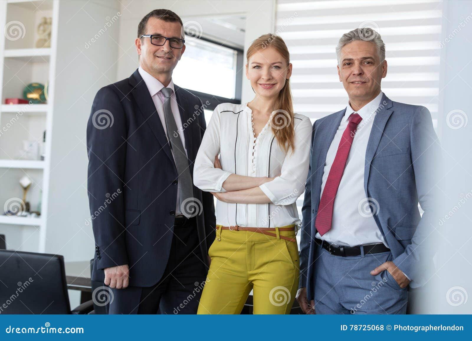 Stående av den säkra unga affärskvinnan med manliga kollegor i regeringsställning
