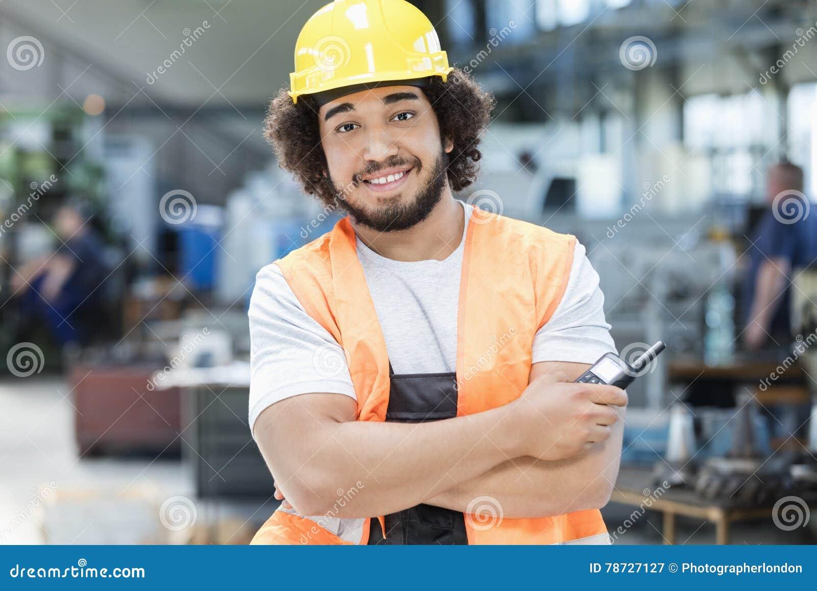 Stående av den säkra unga hållande walkie-talkie för manuell arbetare i metallbransch