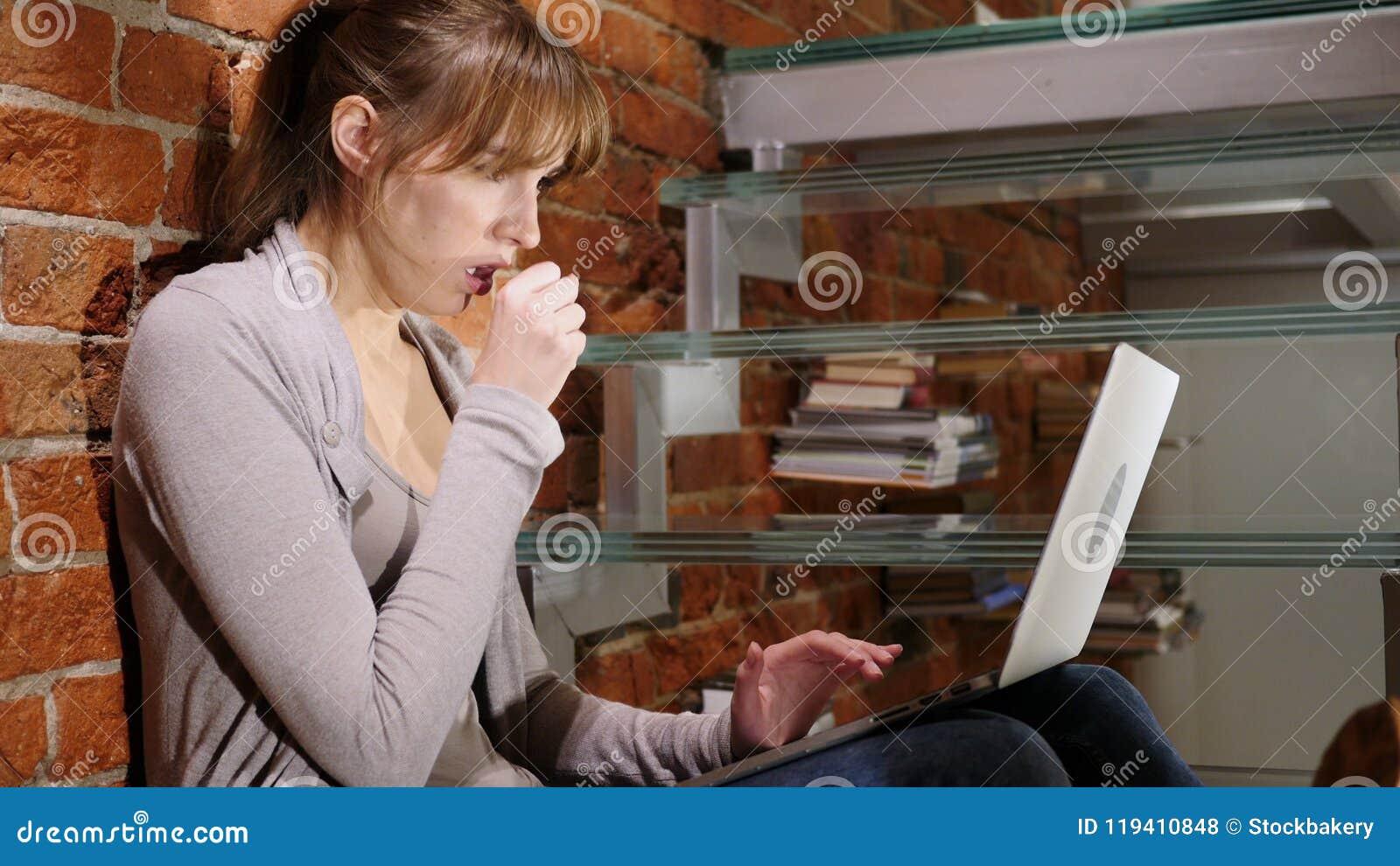 Stående av den sjuka kvinnan som hostar, medan arbeta på bärbara datorn