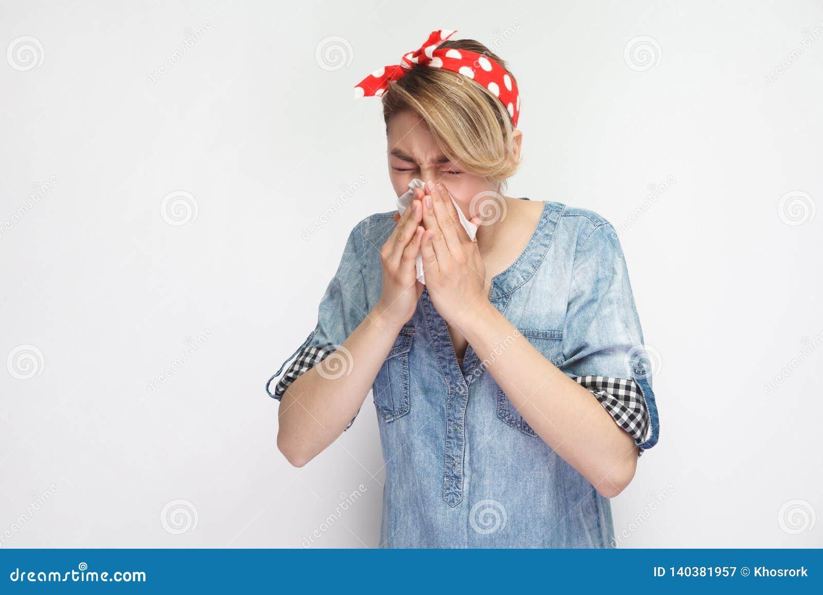 Stående av den sjuka unga kvinnan i tillfällig blå grov bomullstvillskjorta med rött huvudbindelanseende med silkespappret och at