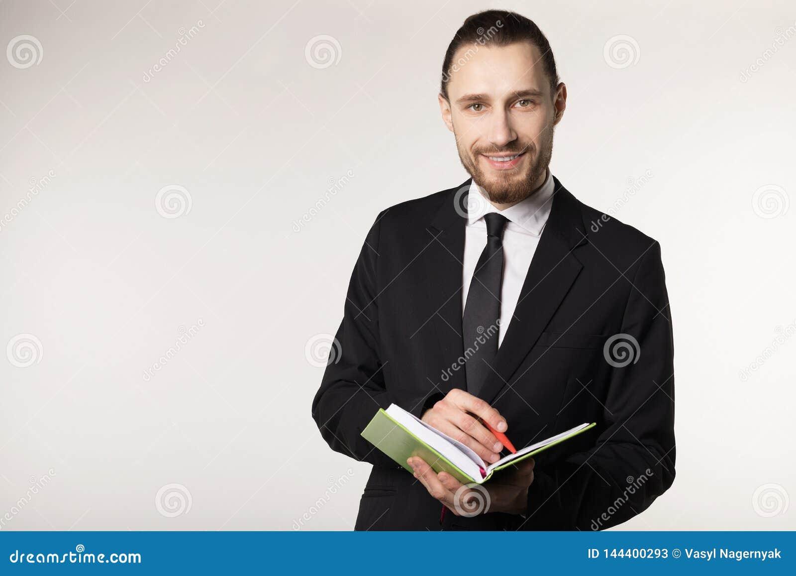 Stående av den skäggiga mannen i svart dräkt och bandet med den moderiktiga frisyren som gör anmärkningar i hans anteckningsbok