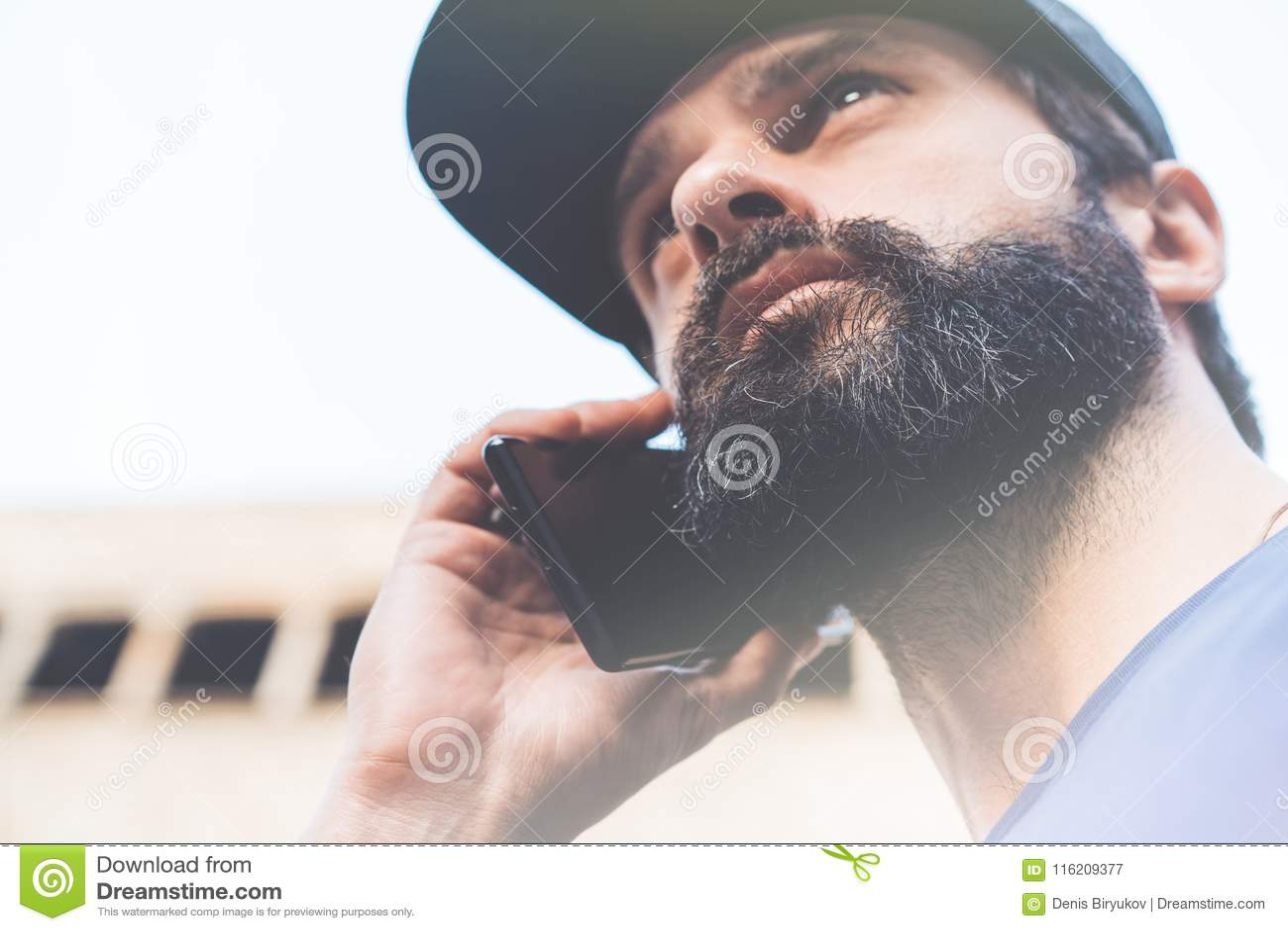 Stående av den skäggiga unga mannen som använder hans smartphone på gatan suddighet bakgrund horisontal Visuella effekter