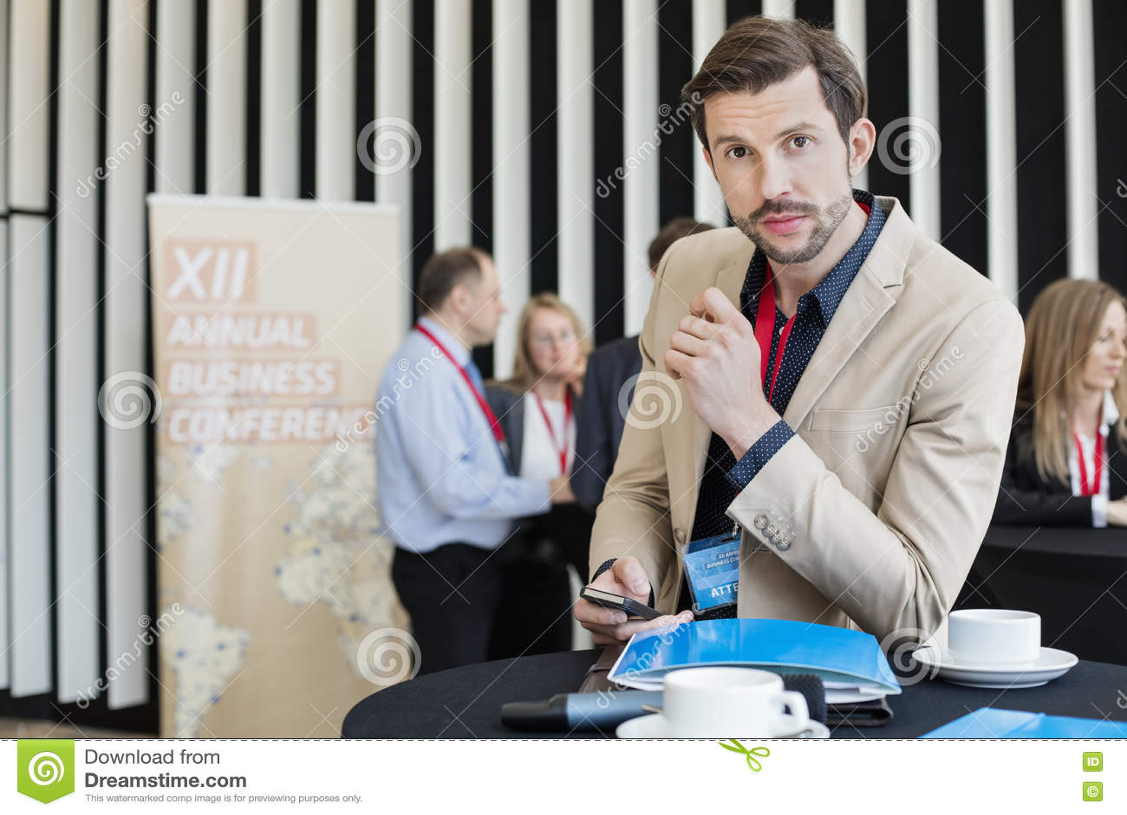 Stående av den smarta telefonen för säkert affärsmaninnehav under kaffeavbrott i konventcentrum