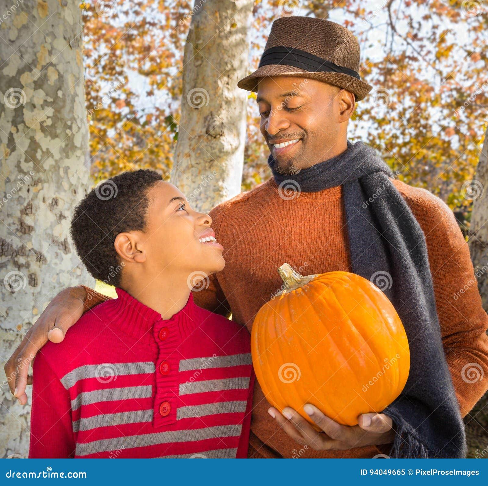 Stående av den stiliga afrikansk amerikanfadern och lyckliga sonen som väljer en pumpa i höst