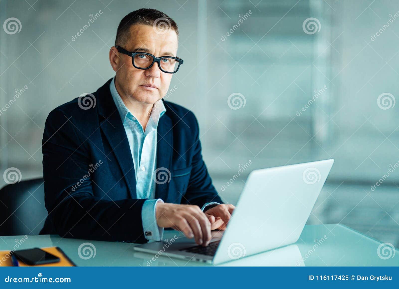 Stående av den stiliga höga affärsmannen som använder en bärbar dator, medan se kameran