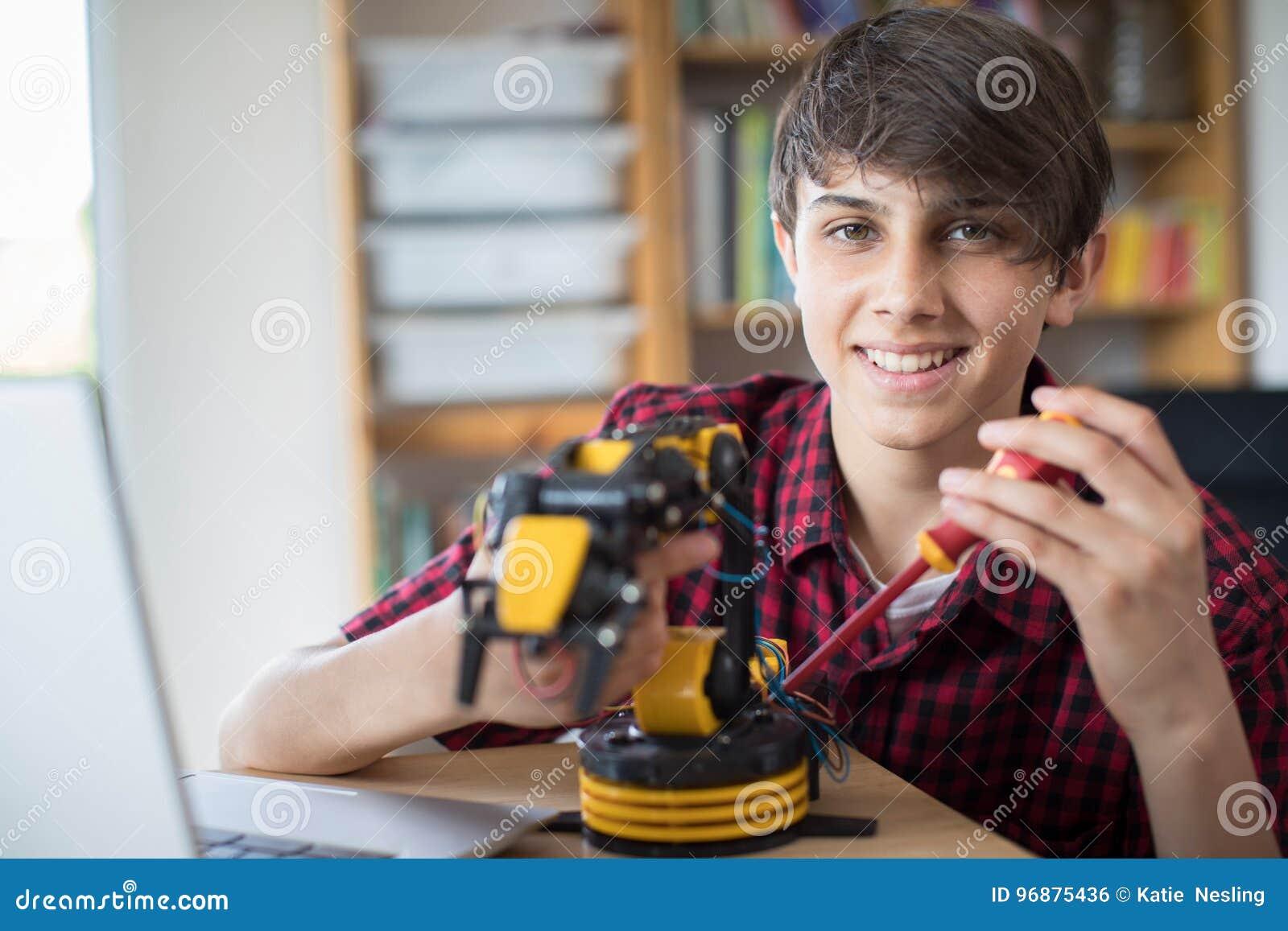 Stående av den tonårs- pojken som bygger den Robotic armen på skolan