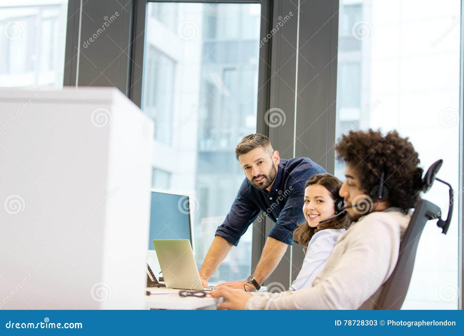 Stående av den unga affärskvinnan med manliga kollegor som i regeringsställning arbetar