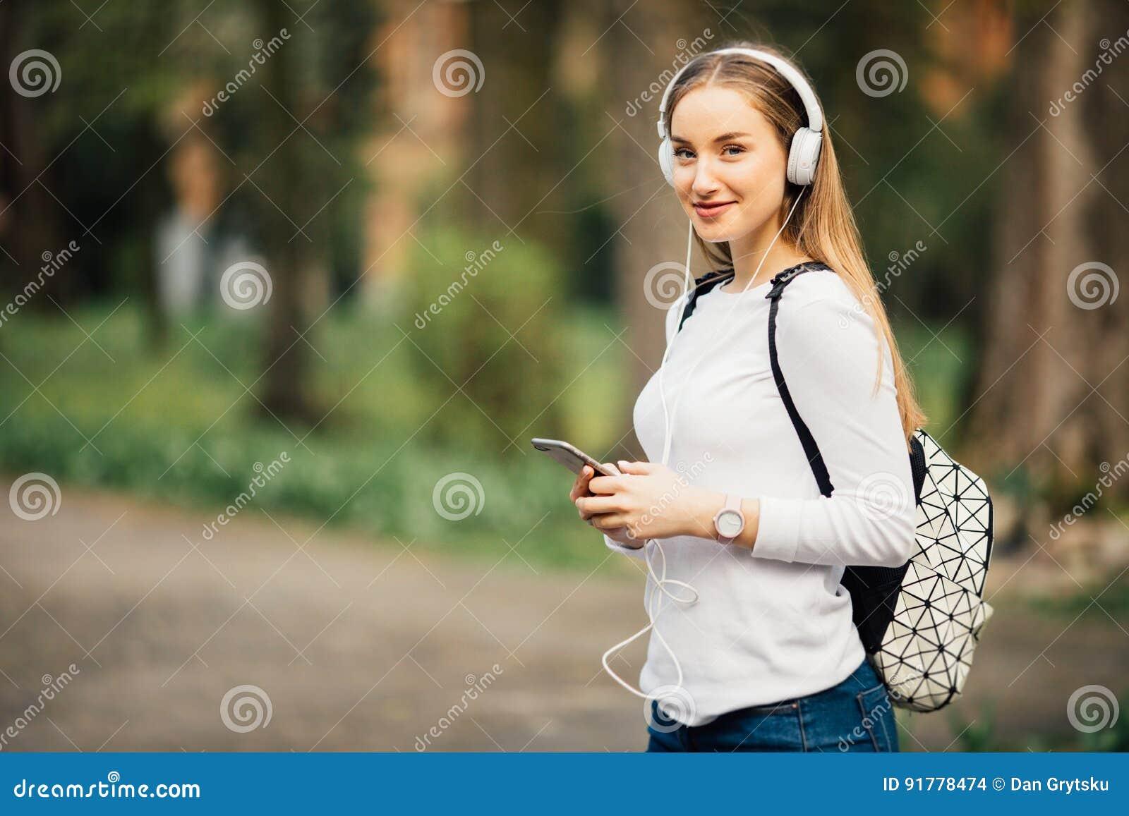 Stående av den unga attraktiva flickan i stads- bakgrund som lyssnar till musik med hörlurar