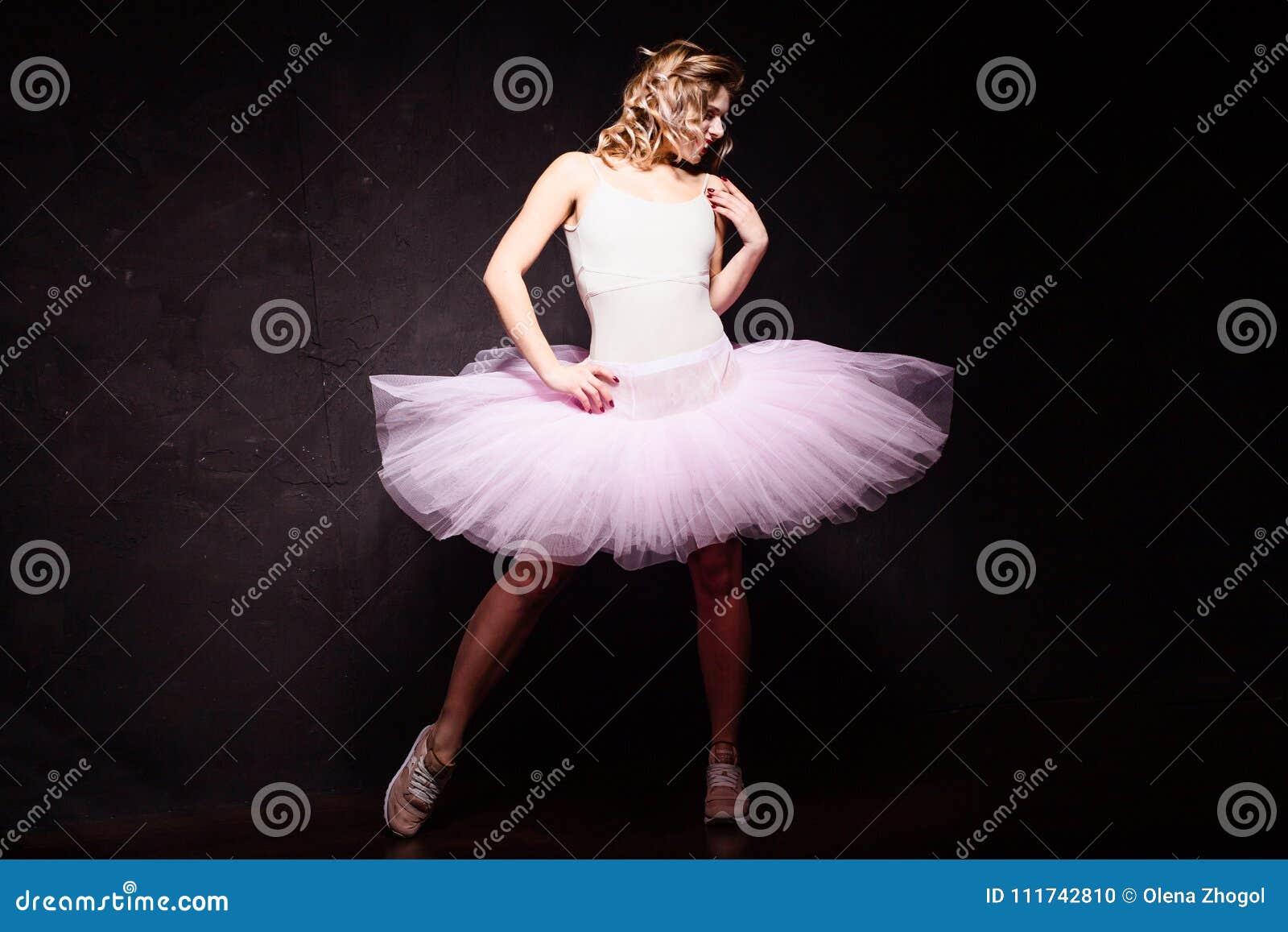 Stående av den unga ballerinaflickan för härlig passform i rosa tillfälliga och balettkläder