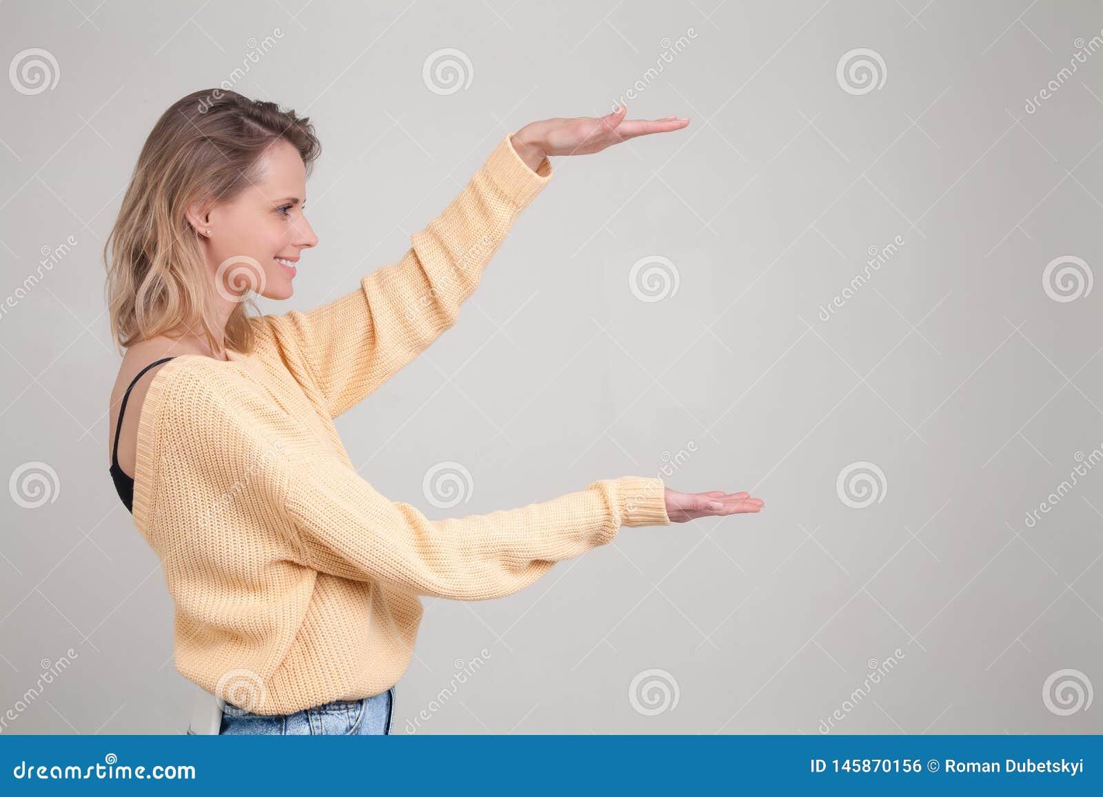 Stående av den unga blonda le kvinnan med den färgade hårkvinnan i gula tröjashower med handlängd av asken Nöjd kvinnlig