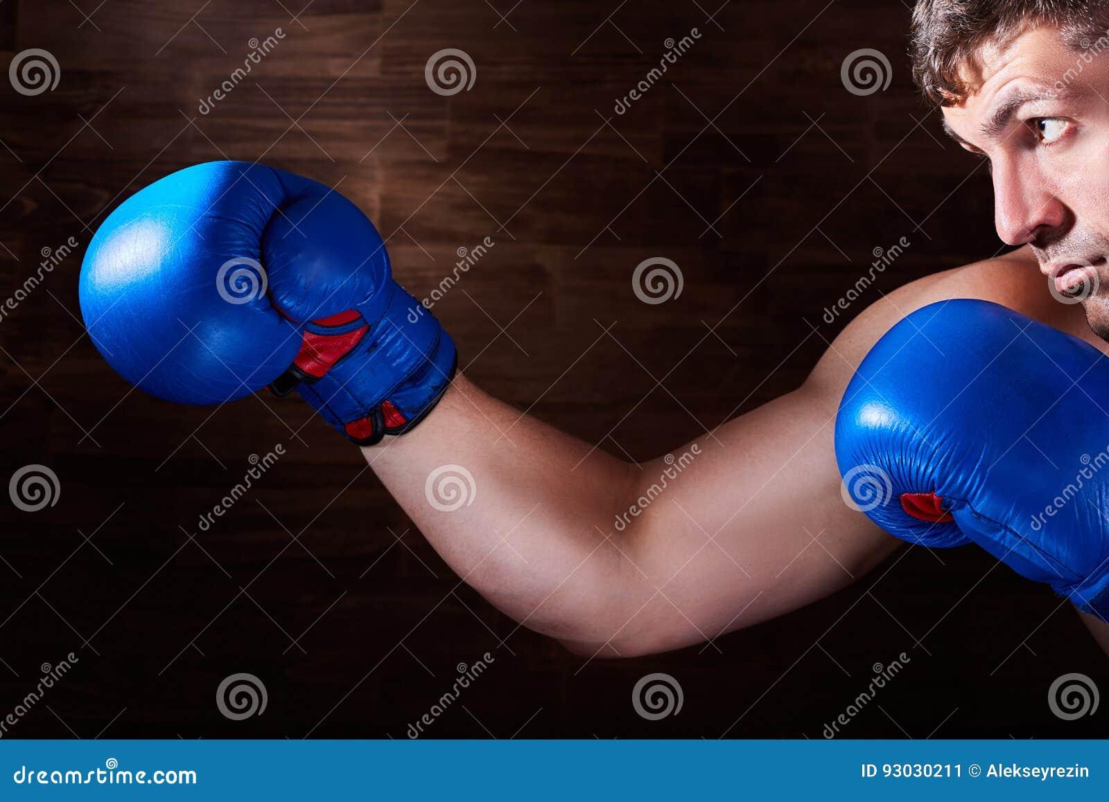 Stående av den unga boxarekämpen med boxninghandskar mot träväggen