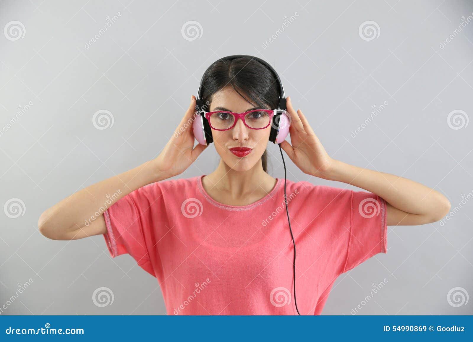 Stående av den unga brunetten som lyssnar till musik som isoleras