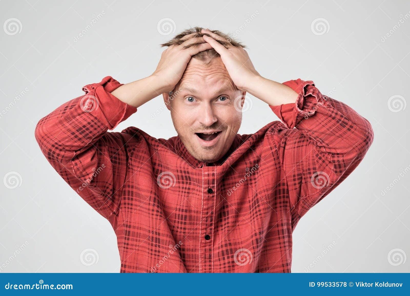Stående av den unga caucasian mannen i röd t-skjorta med chockat ansiktsuttryck som isoleras över vit bakgrund