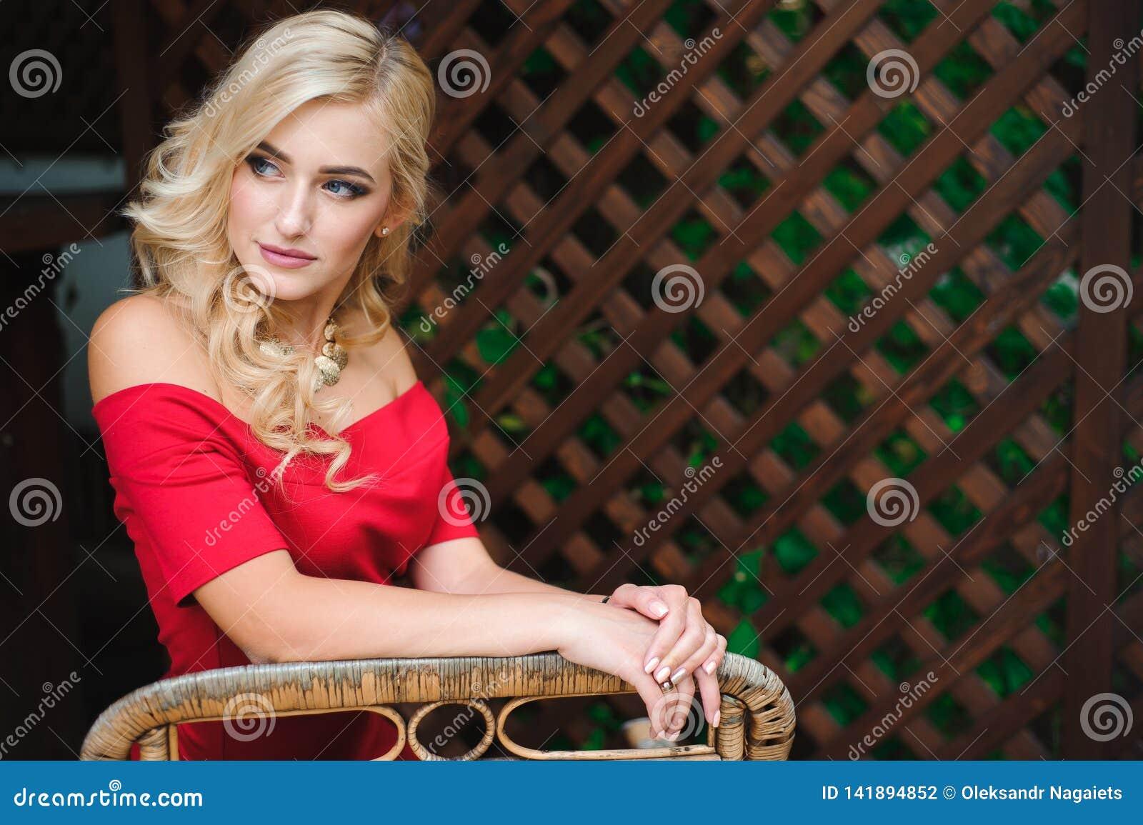 Stående av den unga härliga brunbrända blonda kvinnan i rött sitta för aftonklänning som är utomhus- i gatakafé bara