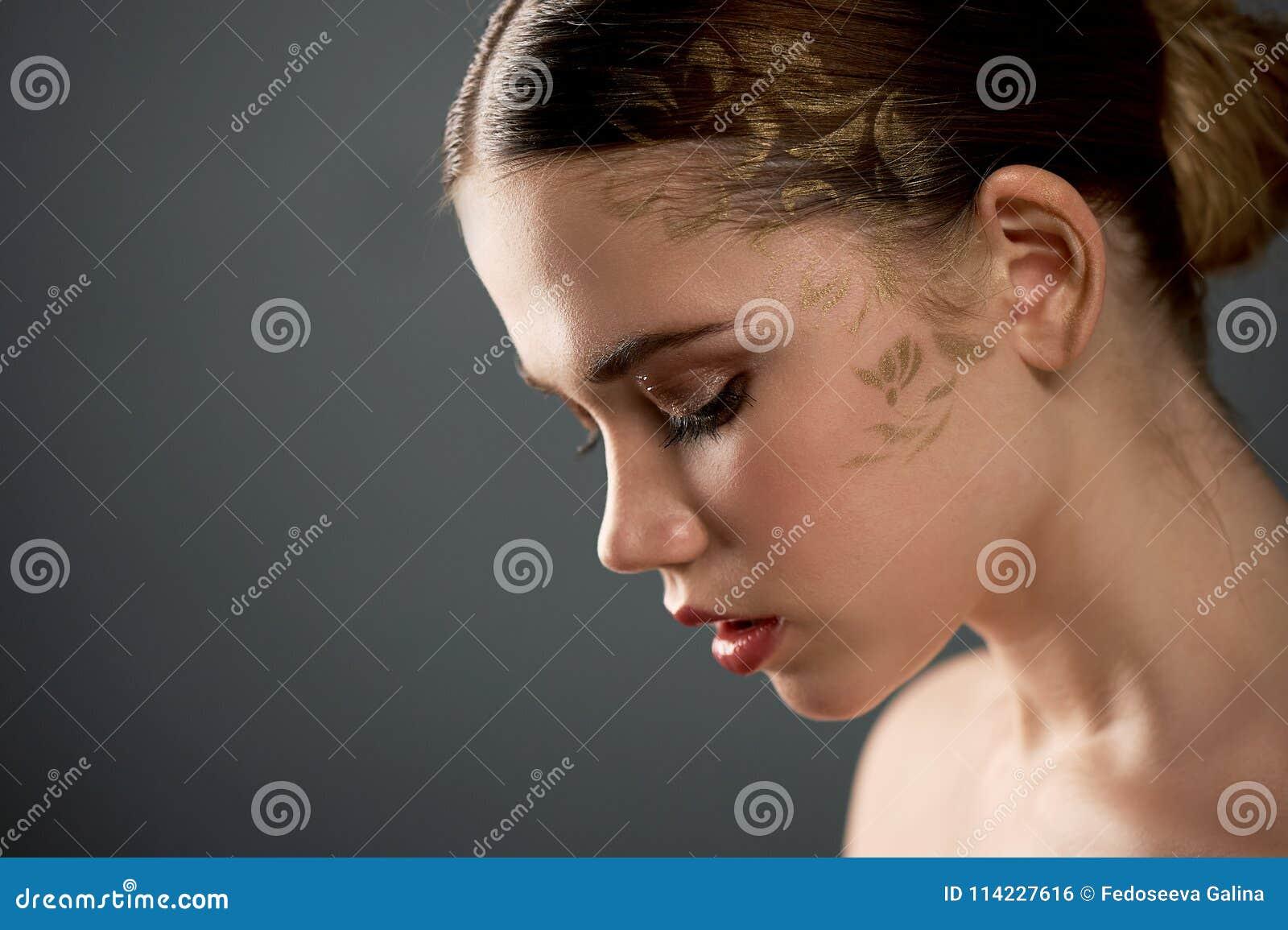 Stående av den unga härliga flickan i studio, med yrkesmässig makeup Skönhetskytte På framsidamodellgulden som besprutas