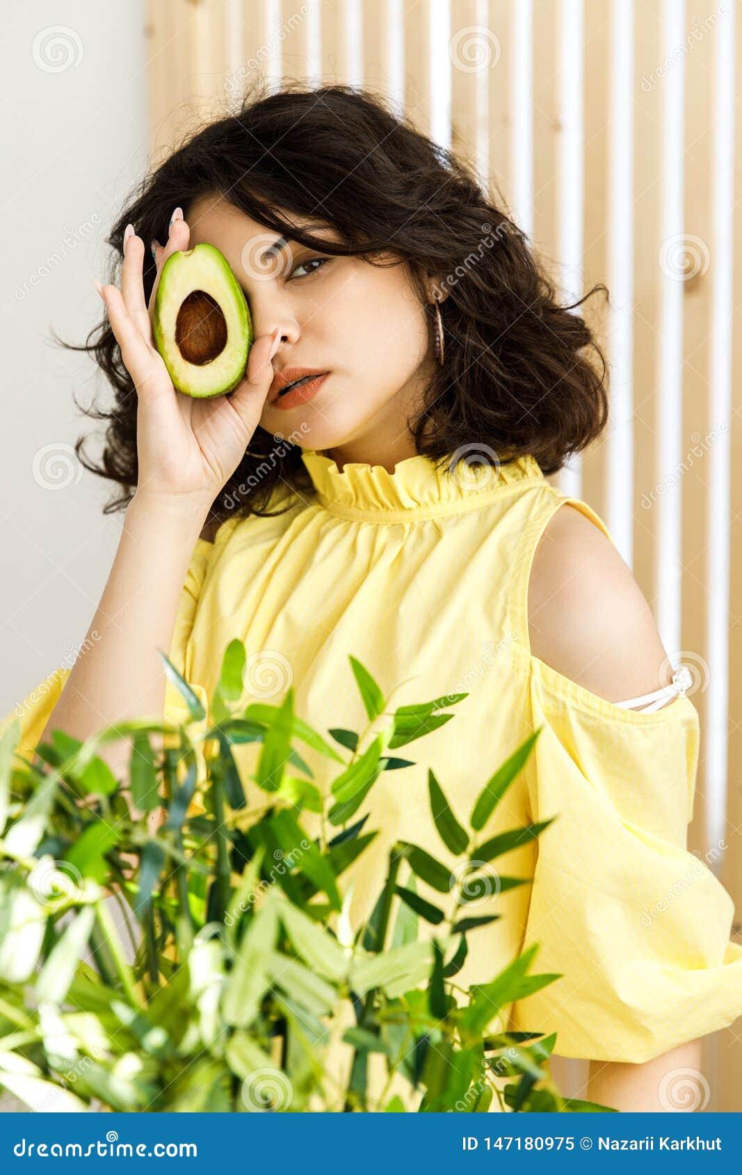 Stående av den unga härliga kvinnan med den mogna läckra avokadot på ljus bakgrund sund mat