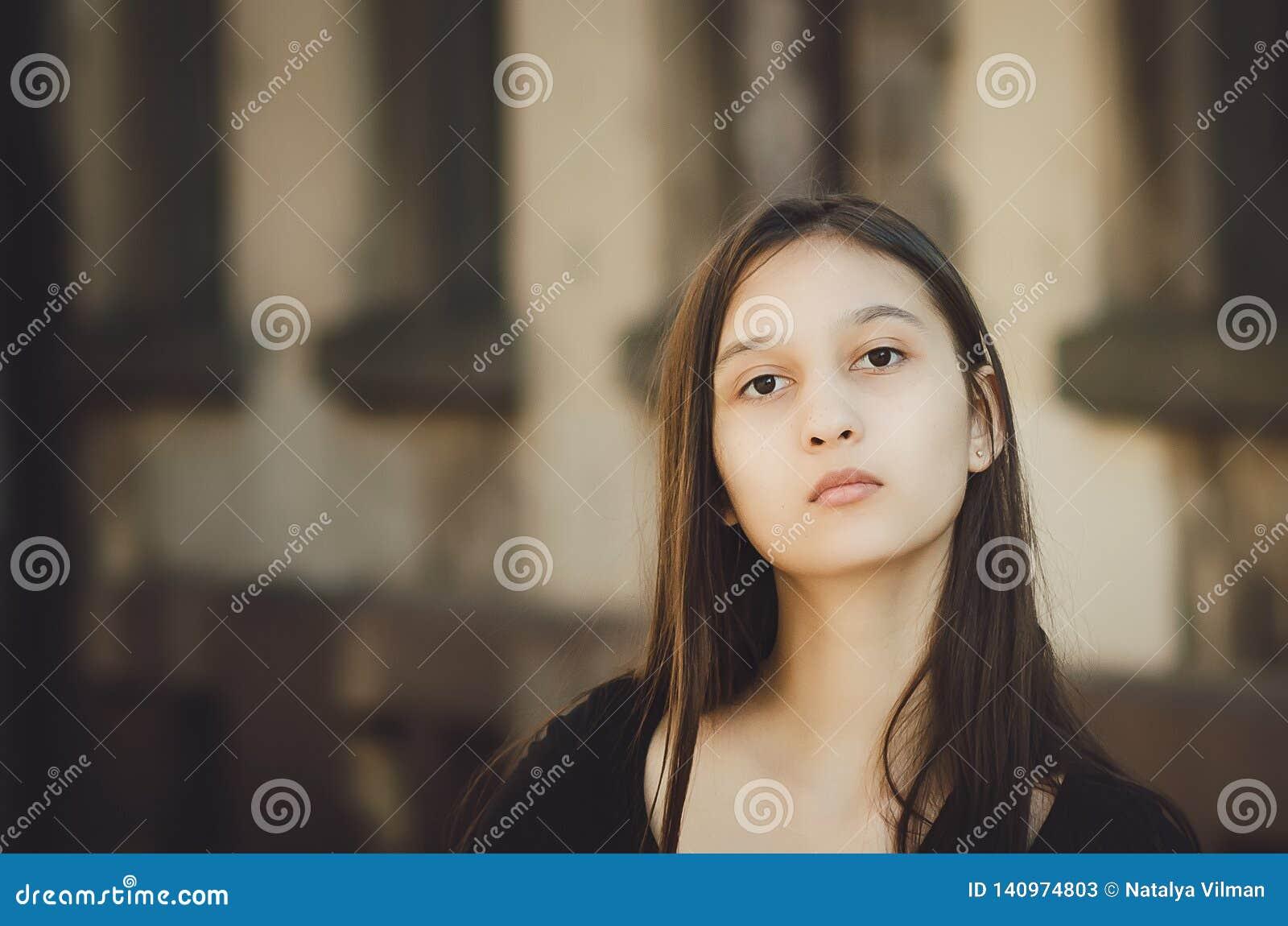 Stående av den unga härliga nätta kvinnan med långt hår som poserar i stad